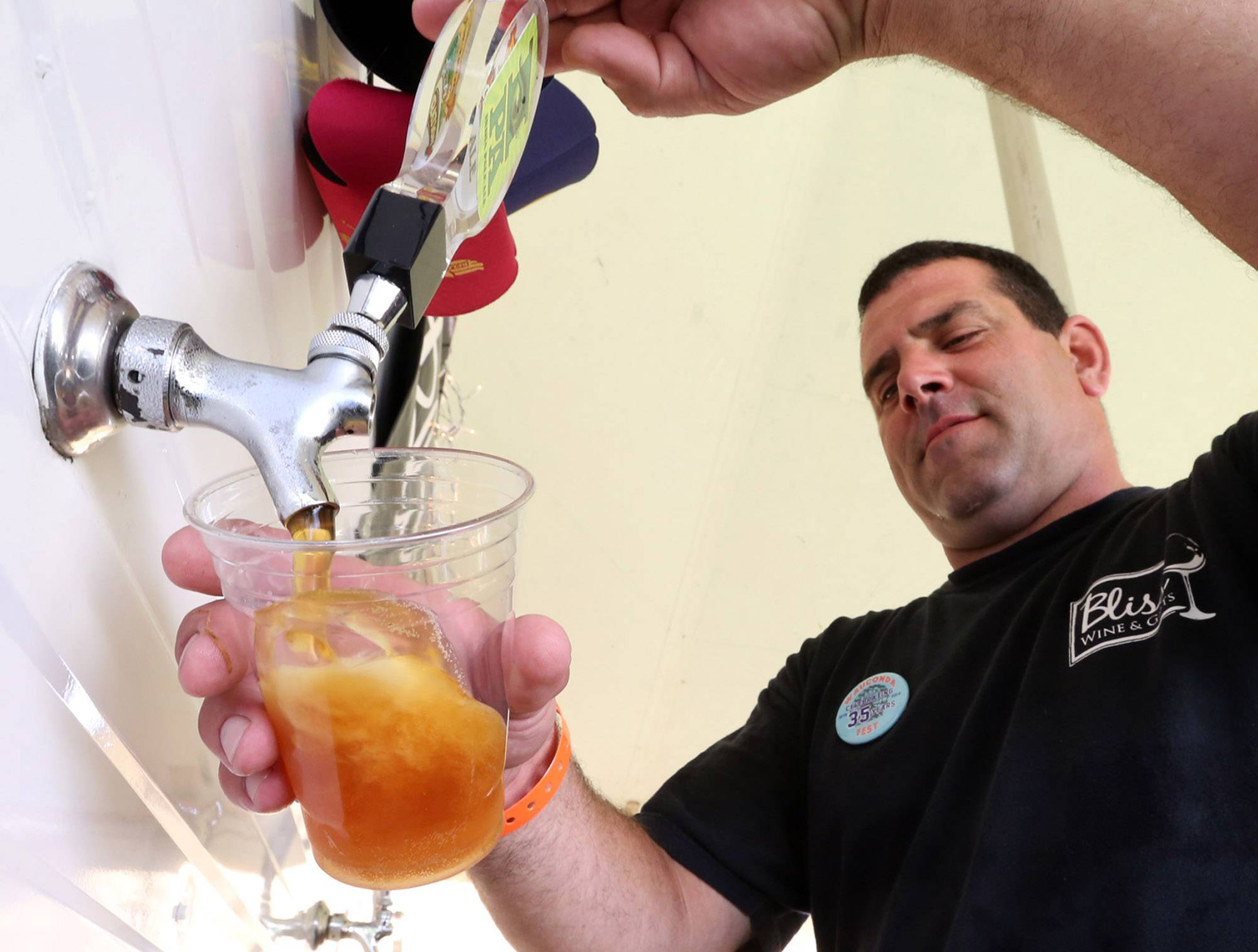 Scott Weisbruch taps an India pale ale in the Bliss Wine and Gifts of Wauconda wine tasting tent at the third day of Wauconda Fest on Saturday.