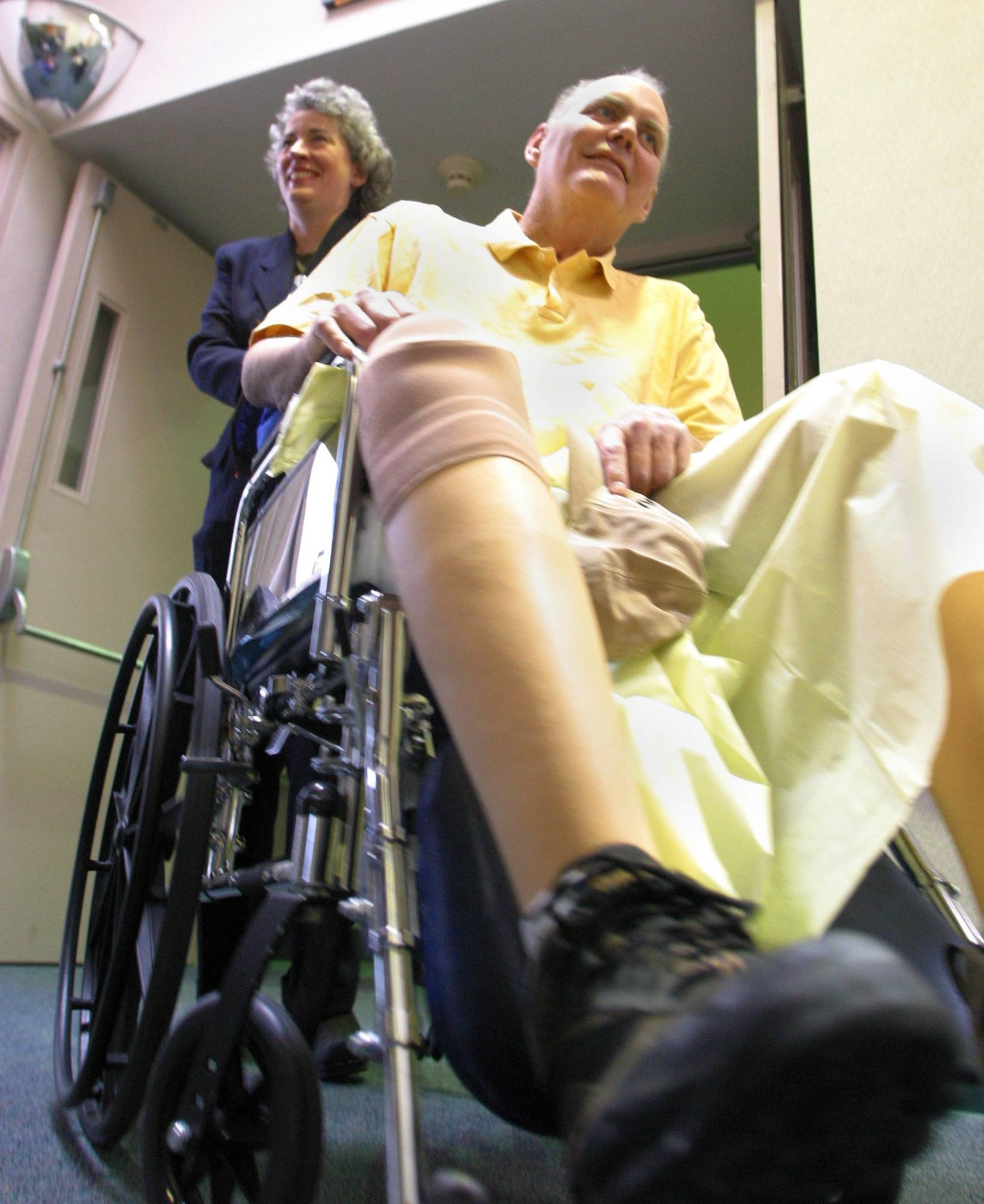 John Tull, right, is wheeled out of a news conference by his wife, Lucinda Marker, at the Kindred Hospital in Albuquerque, N.M.