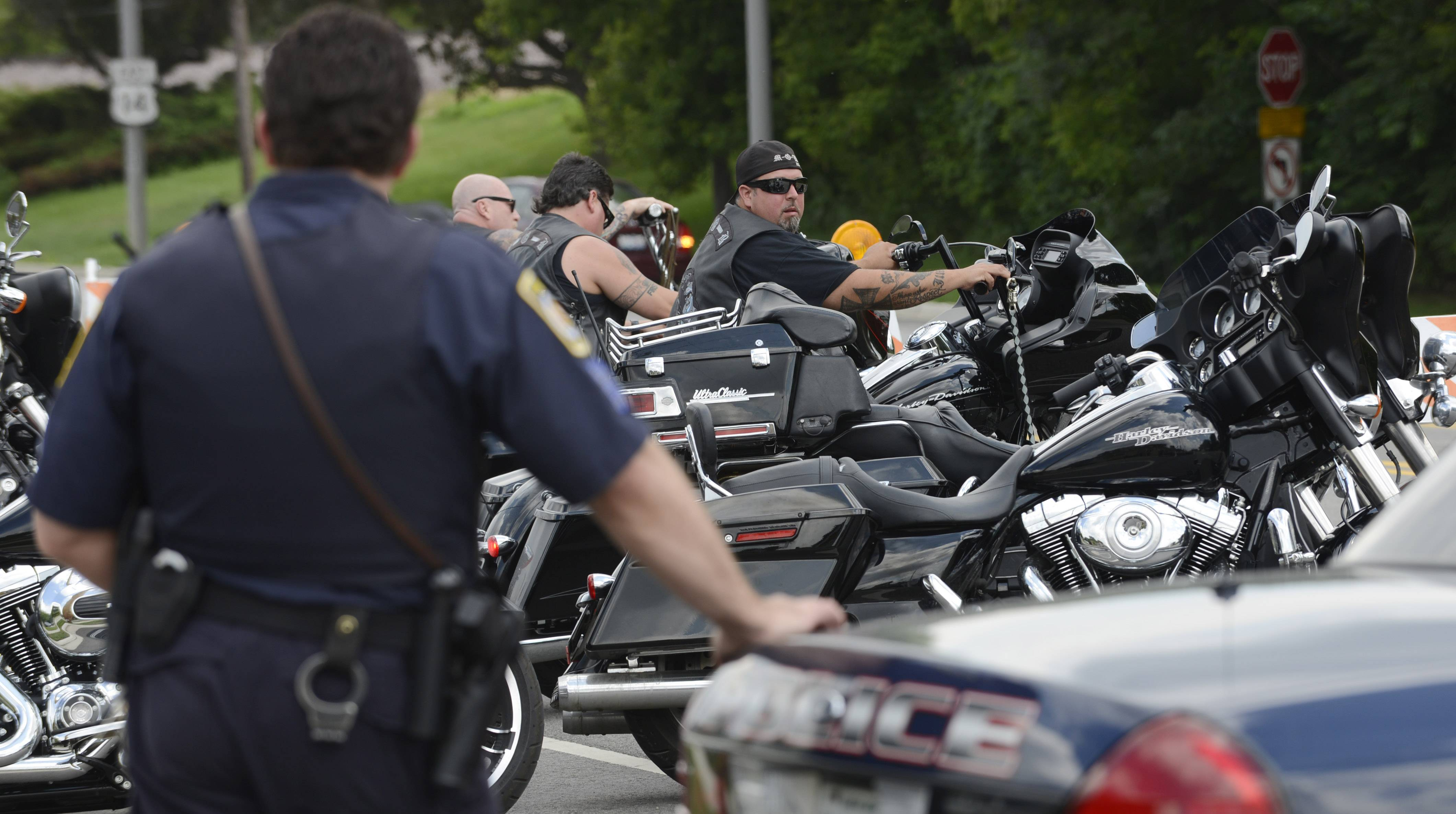 An Arlington Heights police officer stands by his car Saturday as members of the Outlaws motorcycle club arrive for the wake for Douglas Peters.