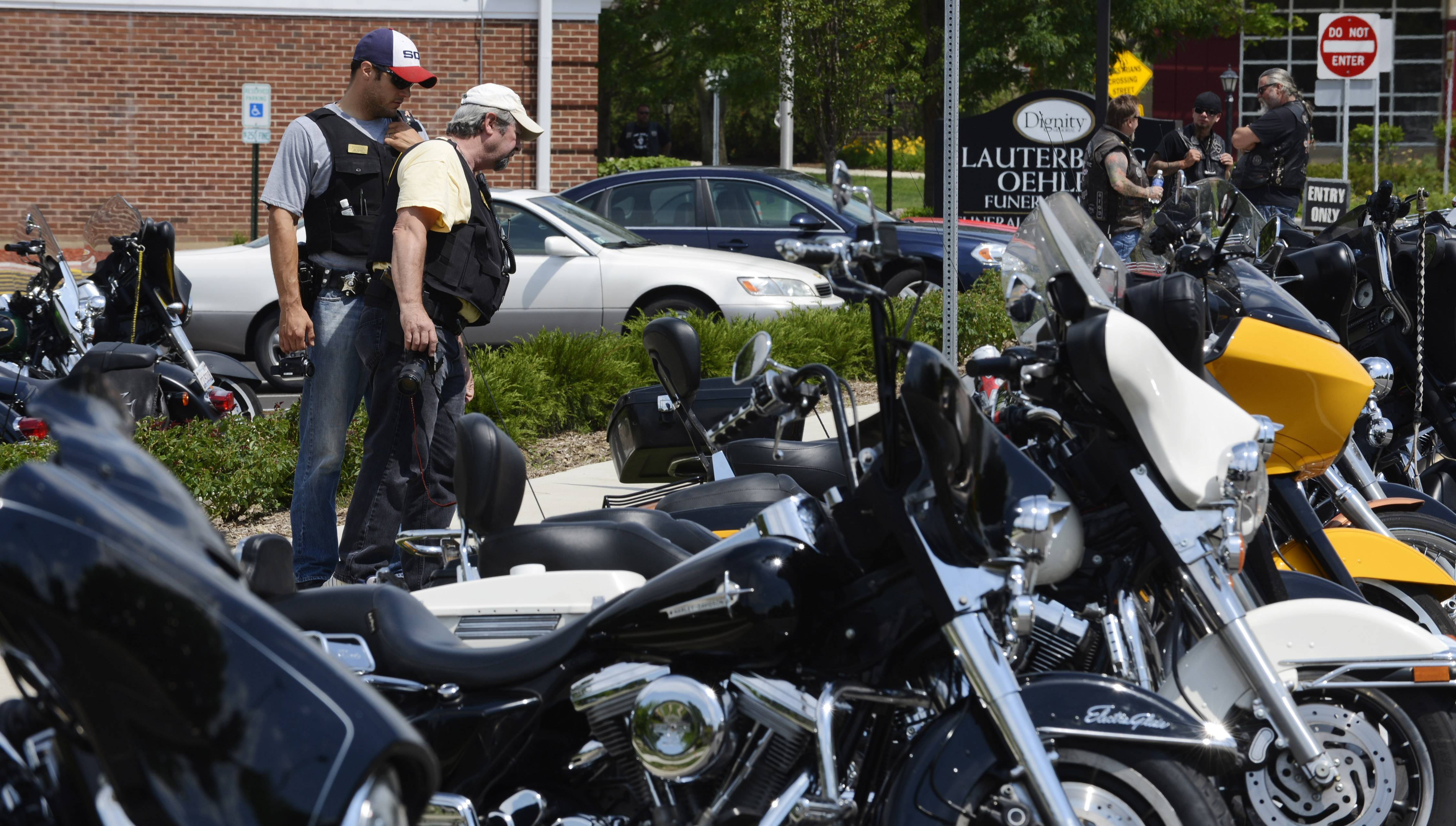 Illinois State Police officers conduct surveillance and photograph motorcycles Saturday outside the wake for Douglas Peters at the Lauterburg-Oehler Funeral Home.