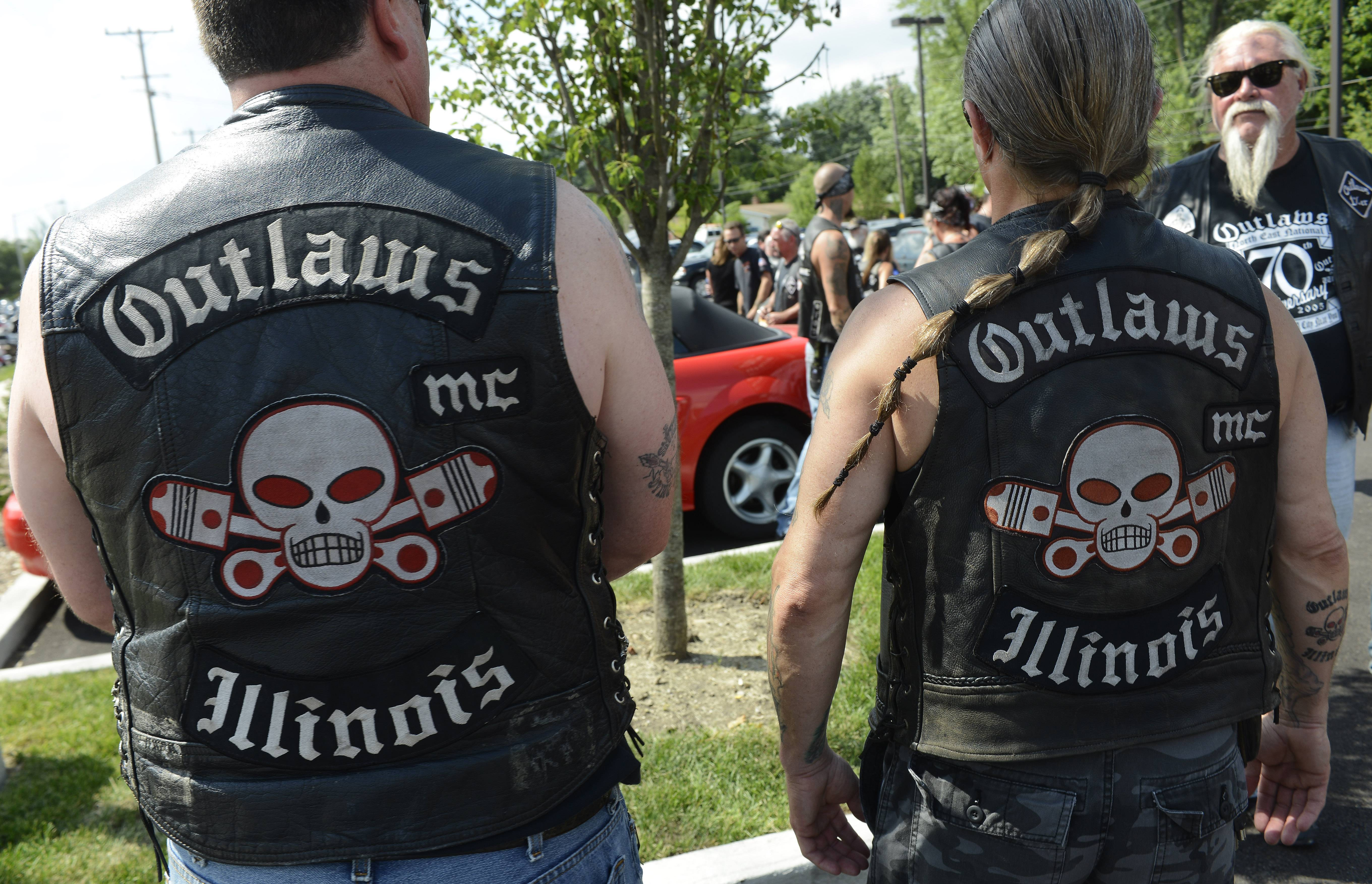 "Club members who identified themselves as ""Westside Dan"" and ""Rosie,"" right, show their patches as members of the Outlaws motorcycle club."