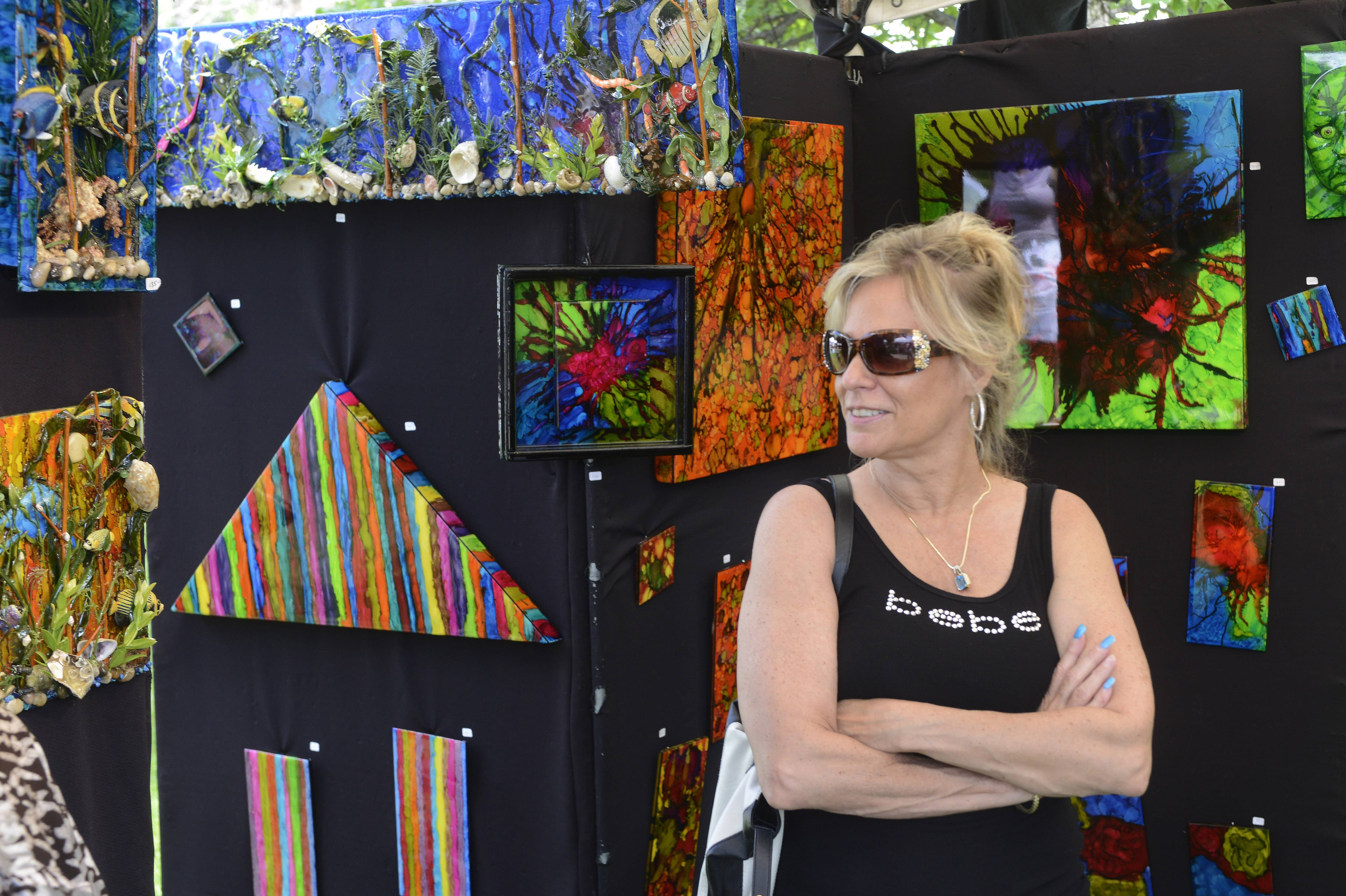 Veronica Payne of South Elgin views mixed media 3D artwork by Robert Aebi of Lathrop, Missouri, during the Arts in Bartlett Festival of the Arts at Bartlett Park Saturday.