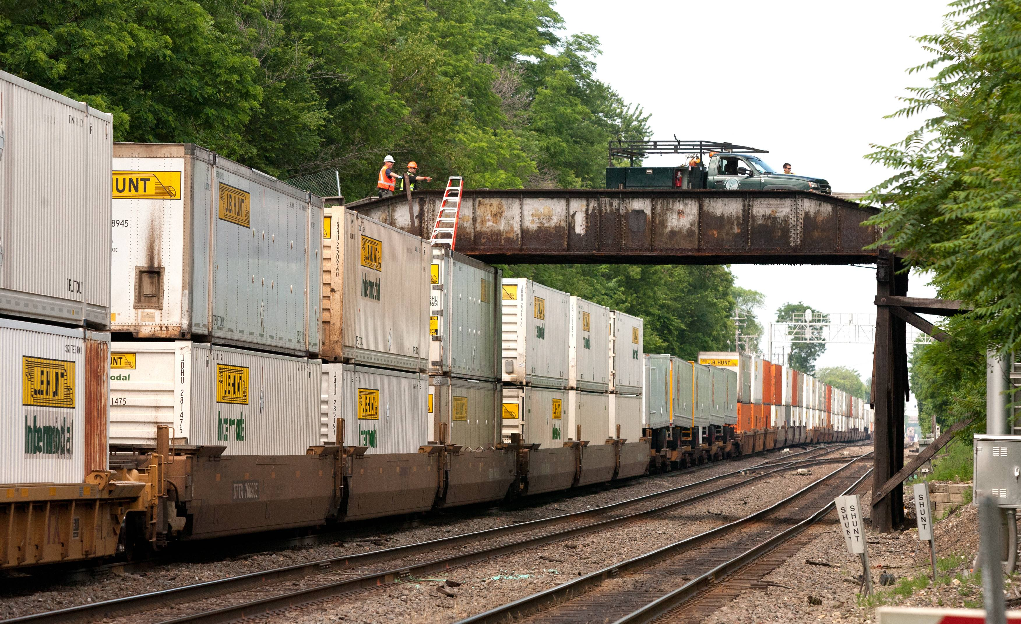 Officials investigate the safety of a bridge in Hinsdale Saturday after a freight train struck a wood beam hanging down from it. The collision disrupted Metra service and caused problems for motorists, but no one was injured.