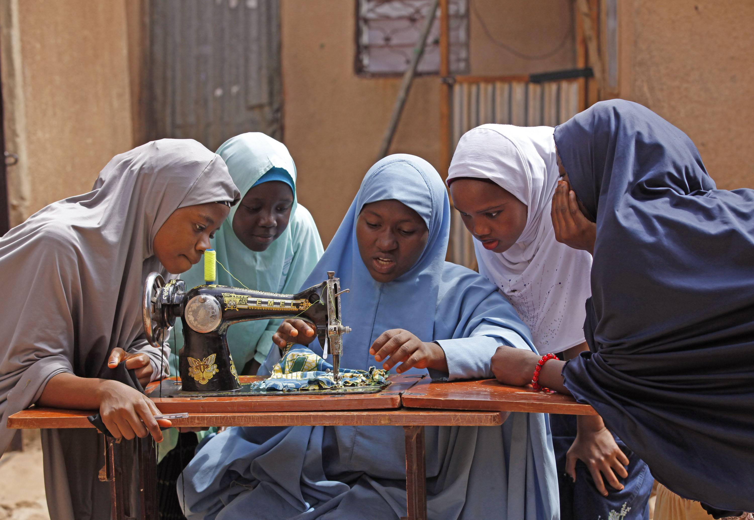 On May 31, Maimuna Abdullahi, center, speaks to classmates as she sews clothes during class at her school in Kaduna, Nigeria. Maimuna wore the scars of an abused woman anywhere: A swollen face, a starved body, and, barely a year after her wedding, a divorce. But for Maimuna, it all happened by the time she was 14. Maimuna is one of thousands of divorced girls in Nigeria who were married as children and then got thrown out by their husbands or simply fled.