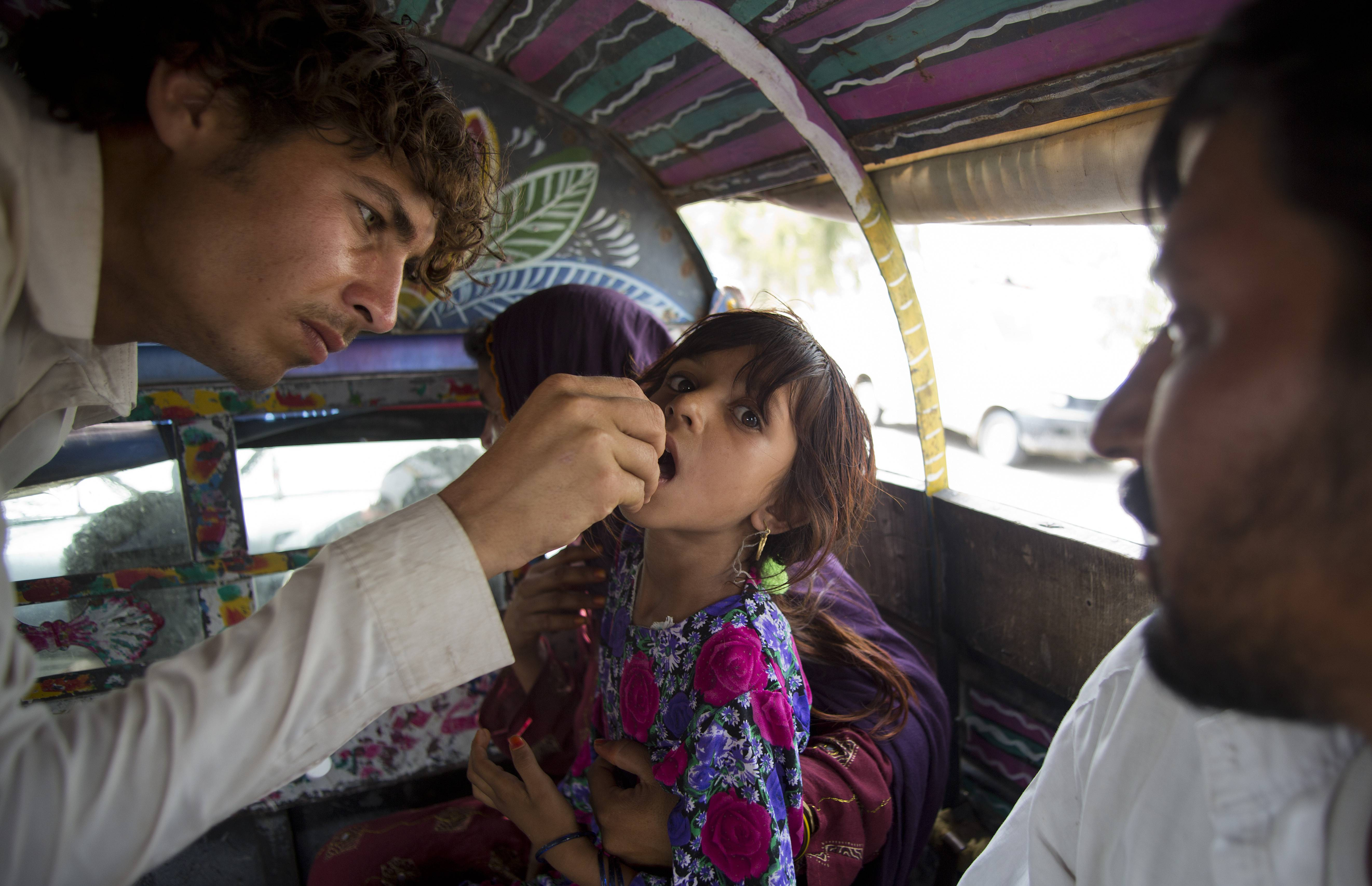 In this photo taken on Friday, June 27, a Pakistani volunteer gives polio vaccine to a displaced tribal girl in Bannu, Pakistan. The rugged Pakistani region of North Waziristan emerged as a hotbed of polio infections after Taliban militants in the isolated area banned immunizations. Now the Pakistani government's offensive against the militants has sent a half-million refugees fleeing the territory, creating both perfect conditions for the disease to spread and a golden opportunity to immunize many thousands of people.