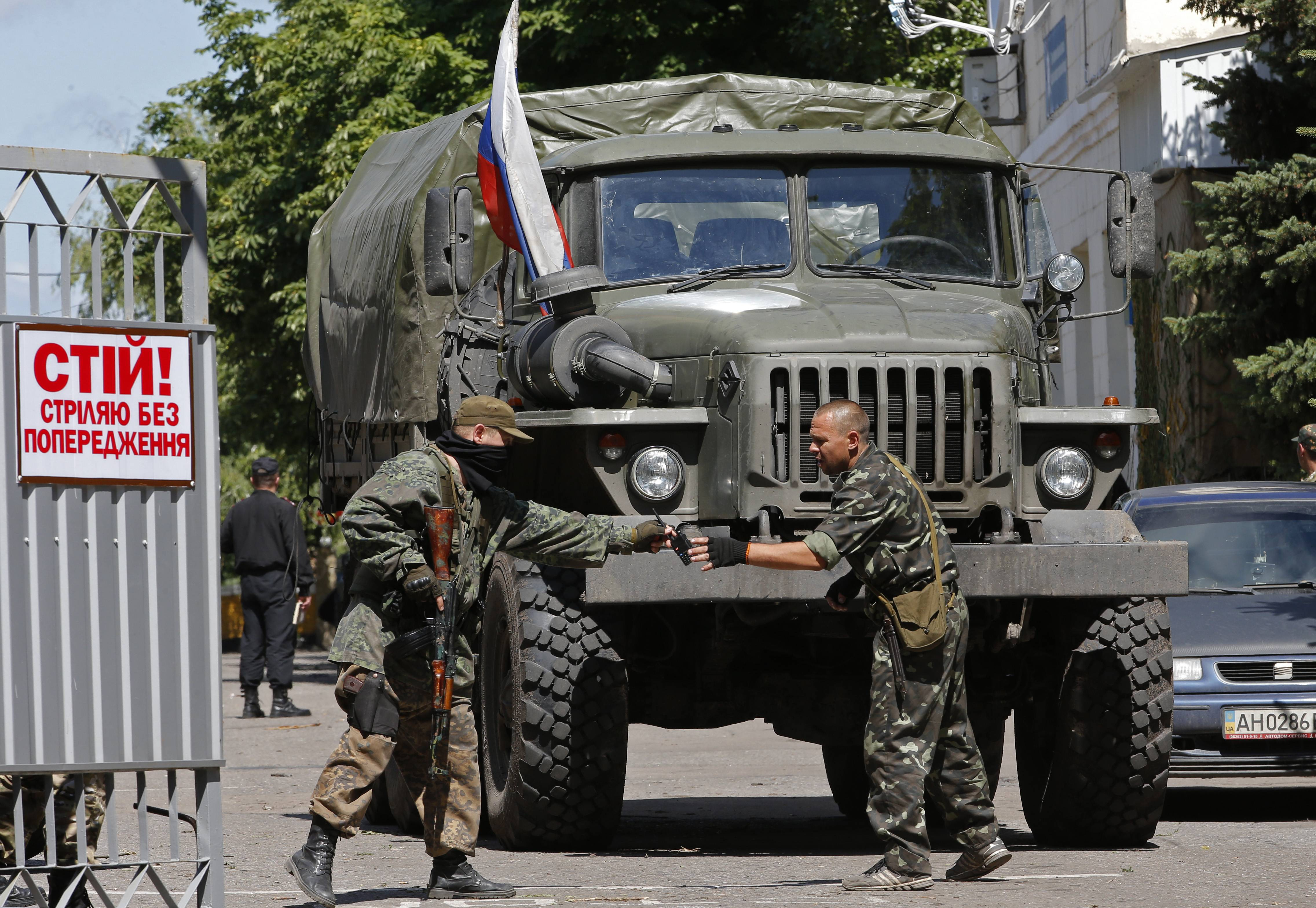 "Pro-Russian fighters stand next to a truck with a Russian flag, inside a captured Ukrainian National Guard unit in the city of Donetsk, eastern Ukraine Saturday, June 28. Russia's foreign minister on Saturday accused the United States of encouraging Ukraine to challenge Moscow and heavily weighing in on the European Union. Speaking in televised remarks Saturday, Sergey Lavrov said that ""our American colleagues still prefer to push the Ukrainian leadership toward a confrontational path."" He added that chances for settling the Ukrainian crisis would have been higher if it only depended on Russia and Europe. The poster reads 'Stop! Shoot without warning!"