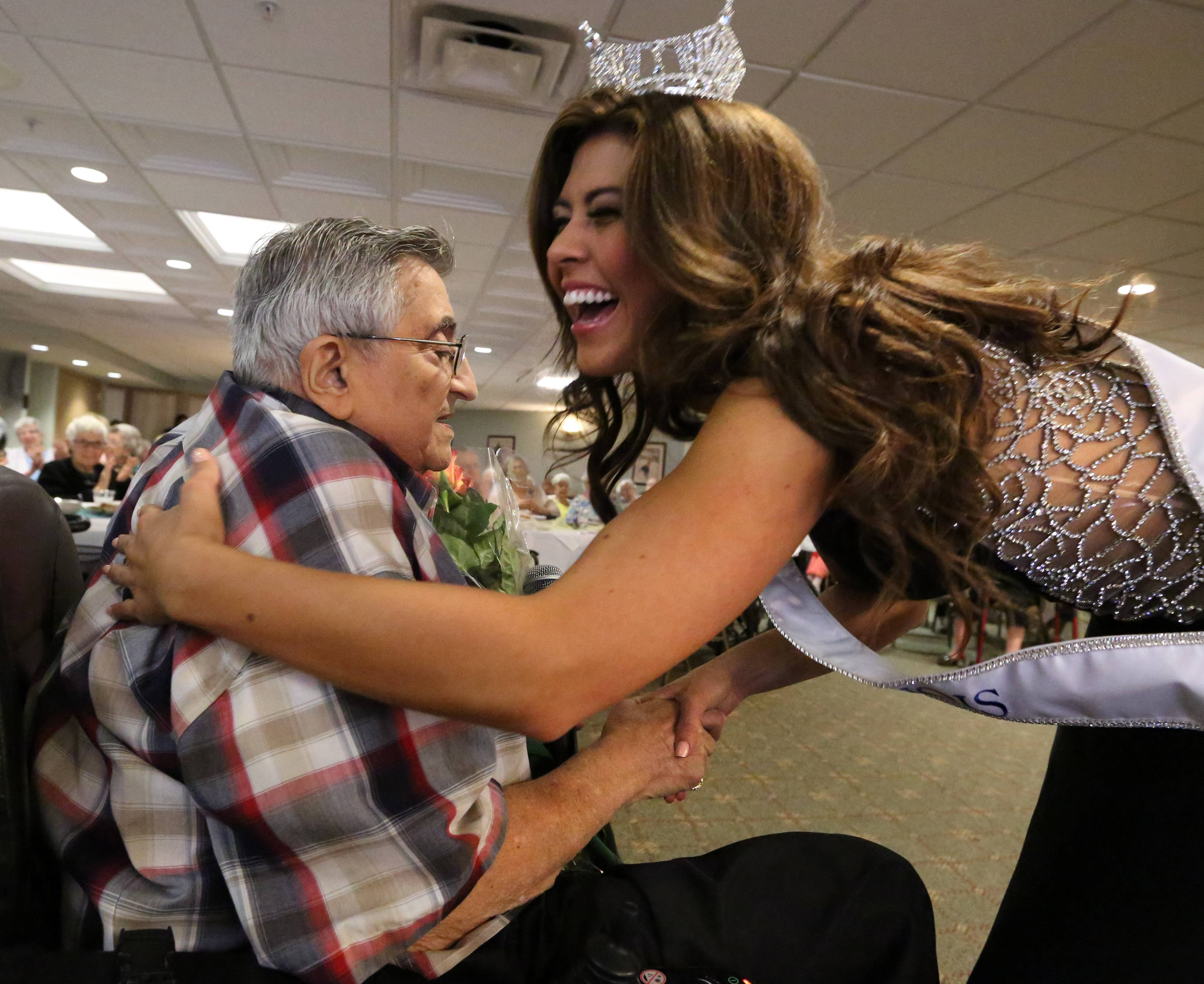 Marisa Buchheit, the new Miss Illinois, gets flowers and a hug from Samuel Kessler, president of the residents association at Brookdale Plaza.