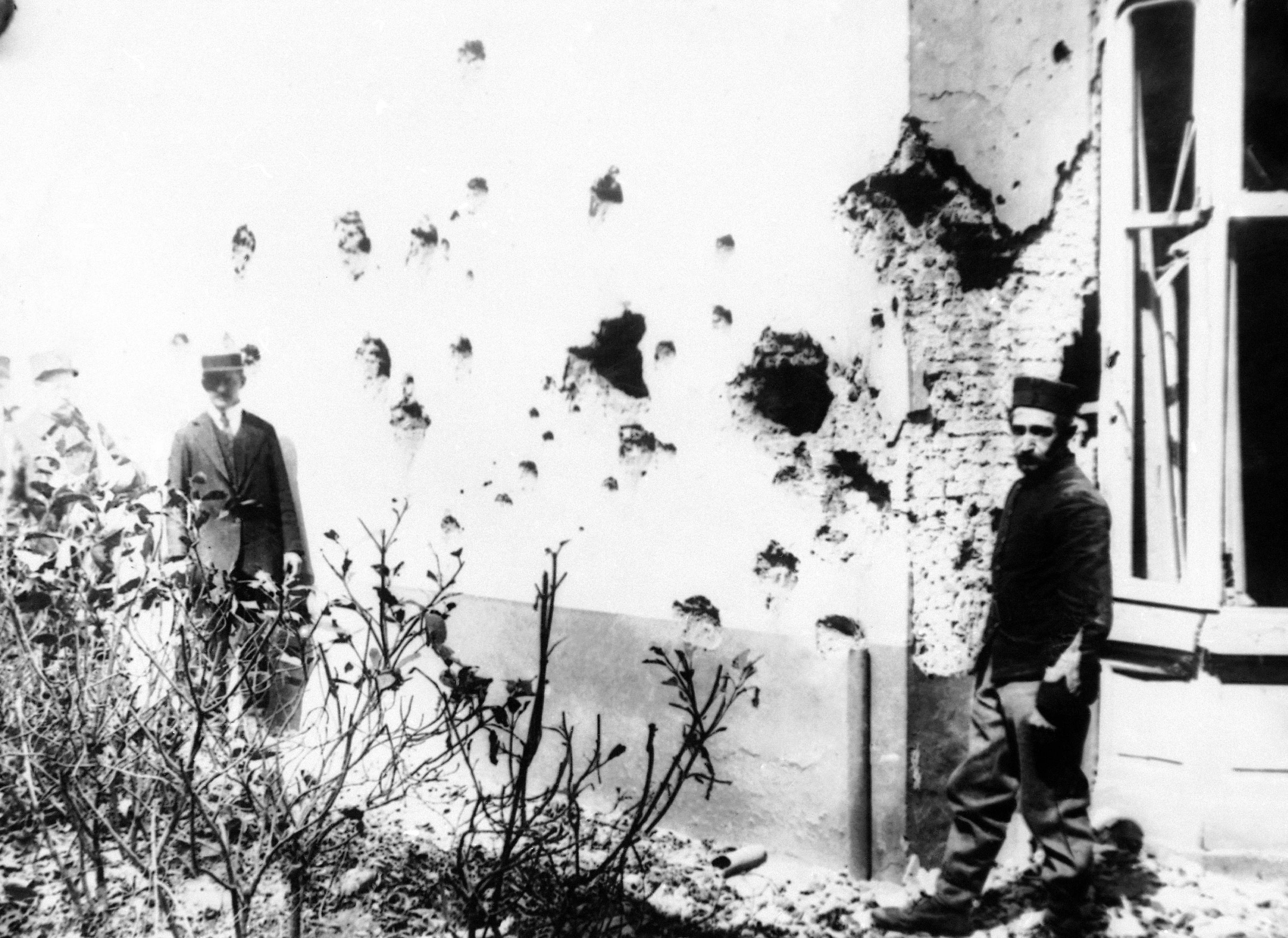 12 OF 100: In this 1914 file photo, a man stands next to a building damaged by shrapnel from bombs dropped from a Zeppelin in Antwerp, Belgium. Antwerp was damaged heavily during World War I.