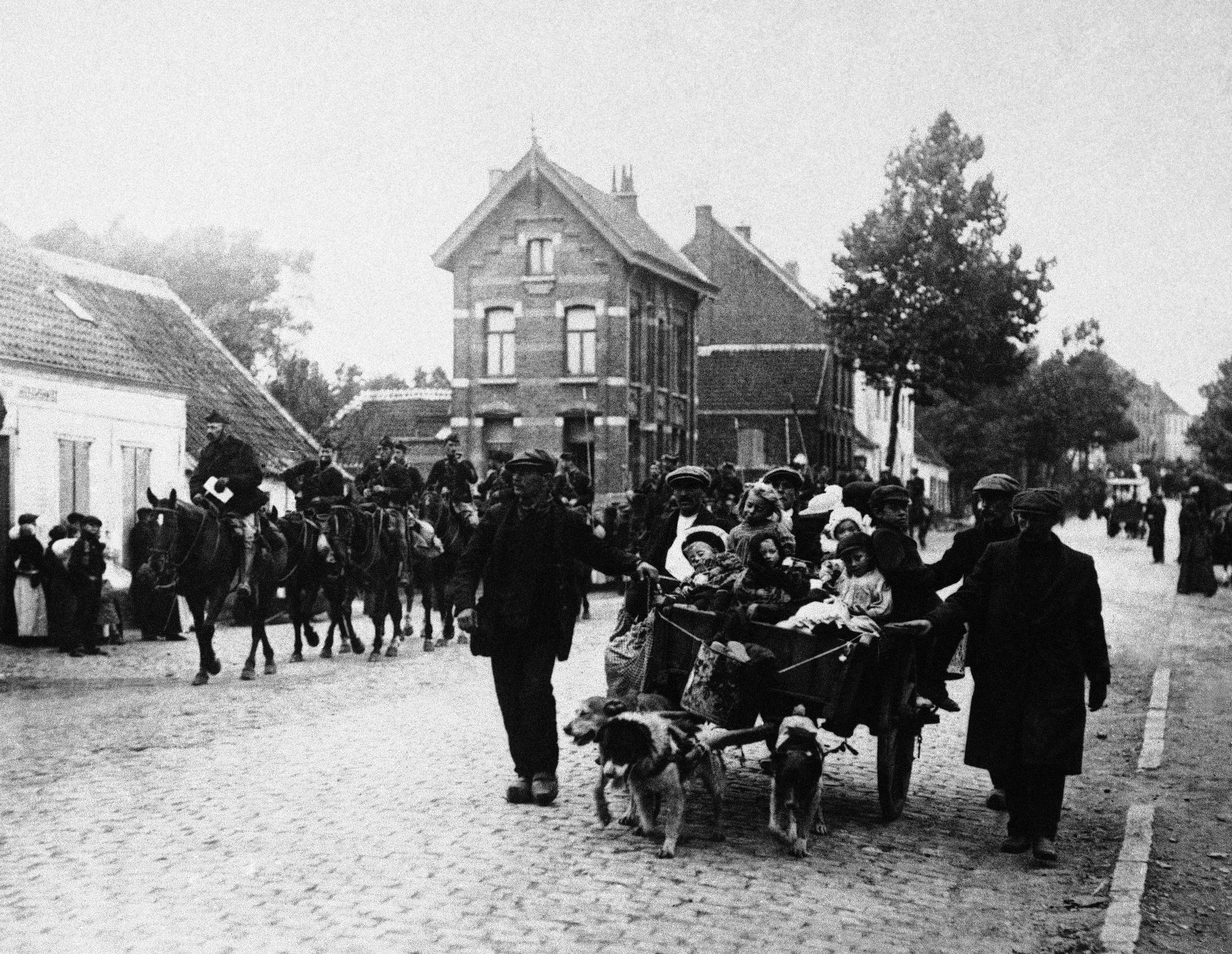 19 OF 100: In this October 14, 1914, file photo, Belgian civilians and a cavalry detail move out of the pathway of the German advance during World War I in Antwerp, Belgium.