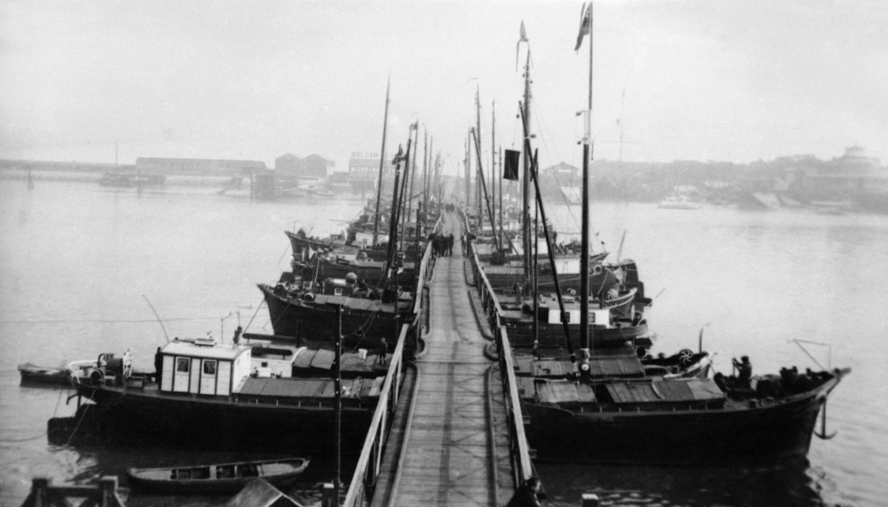 20 OF 100: In this 1914 file photo, small boats, pushed together, create a pontoon bridge over the Scheldt River in Antwerp, Belgium. The bridge was constructed during World War I for residents and troops to escape the German army.