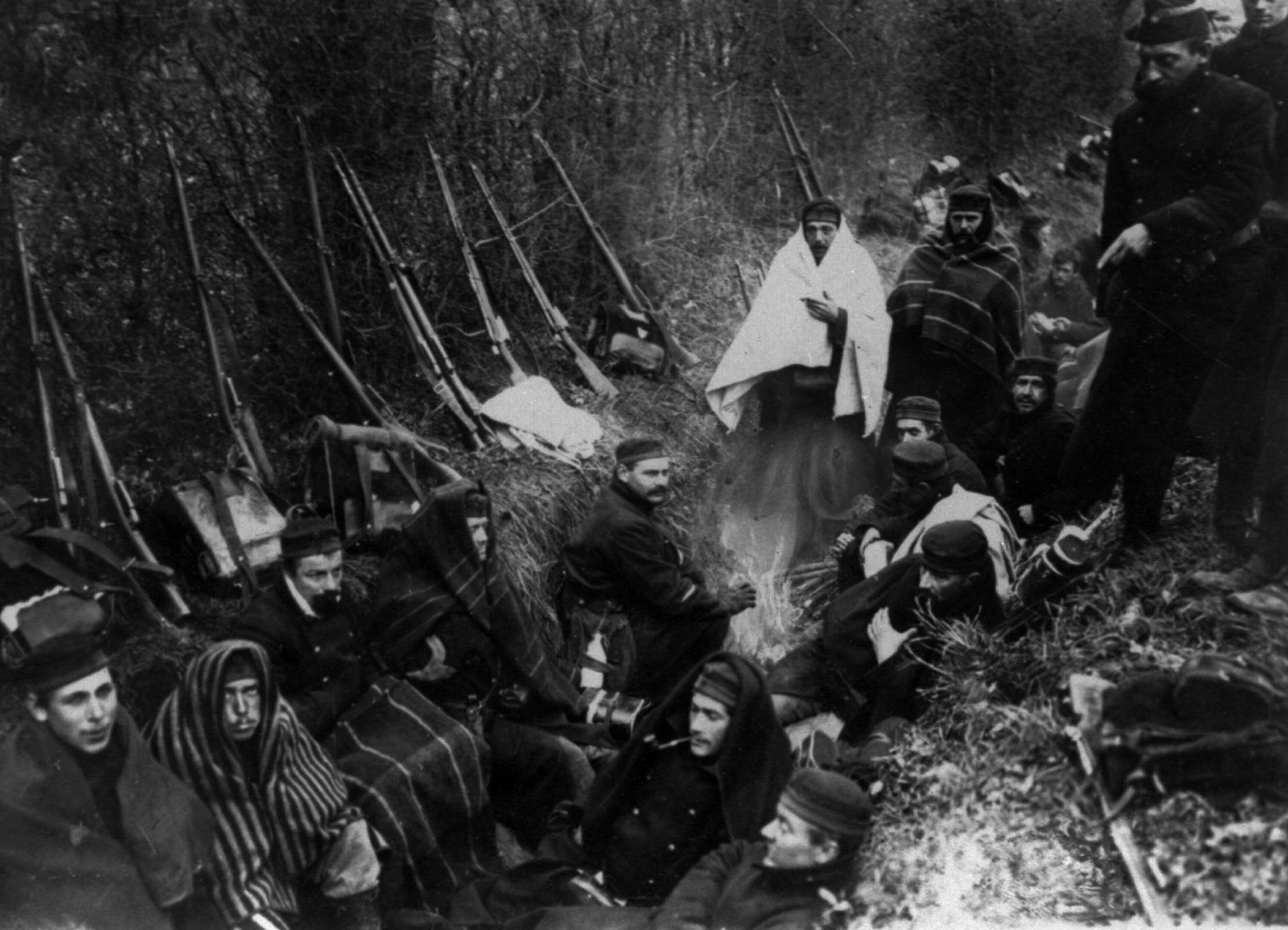 21 OF 100: In this 1914 file photo, Allied troops huddle in a trench around a tiny fire near Ypres, Belgium.