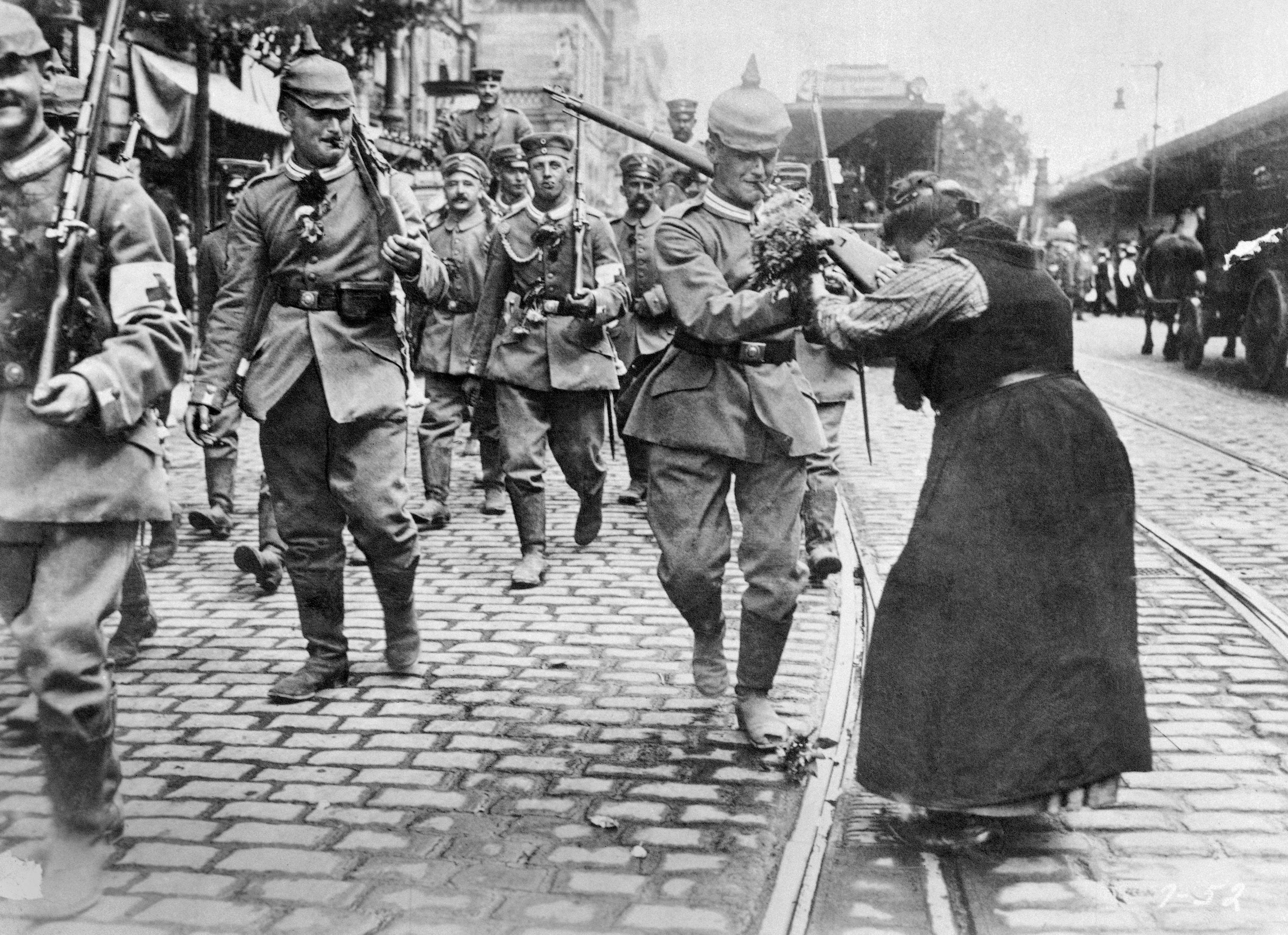 FOUR OF 100:In this undated file photo, Prussian soldiers leaving Berlin for the front are given flowers by a woman during World War I.