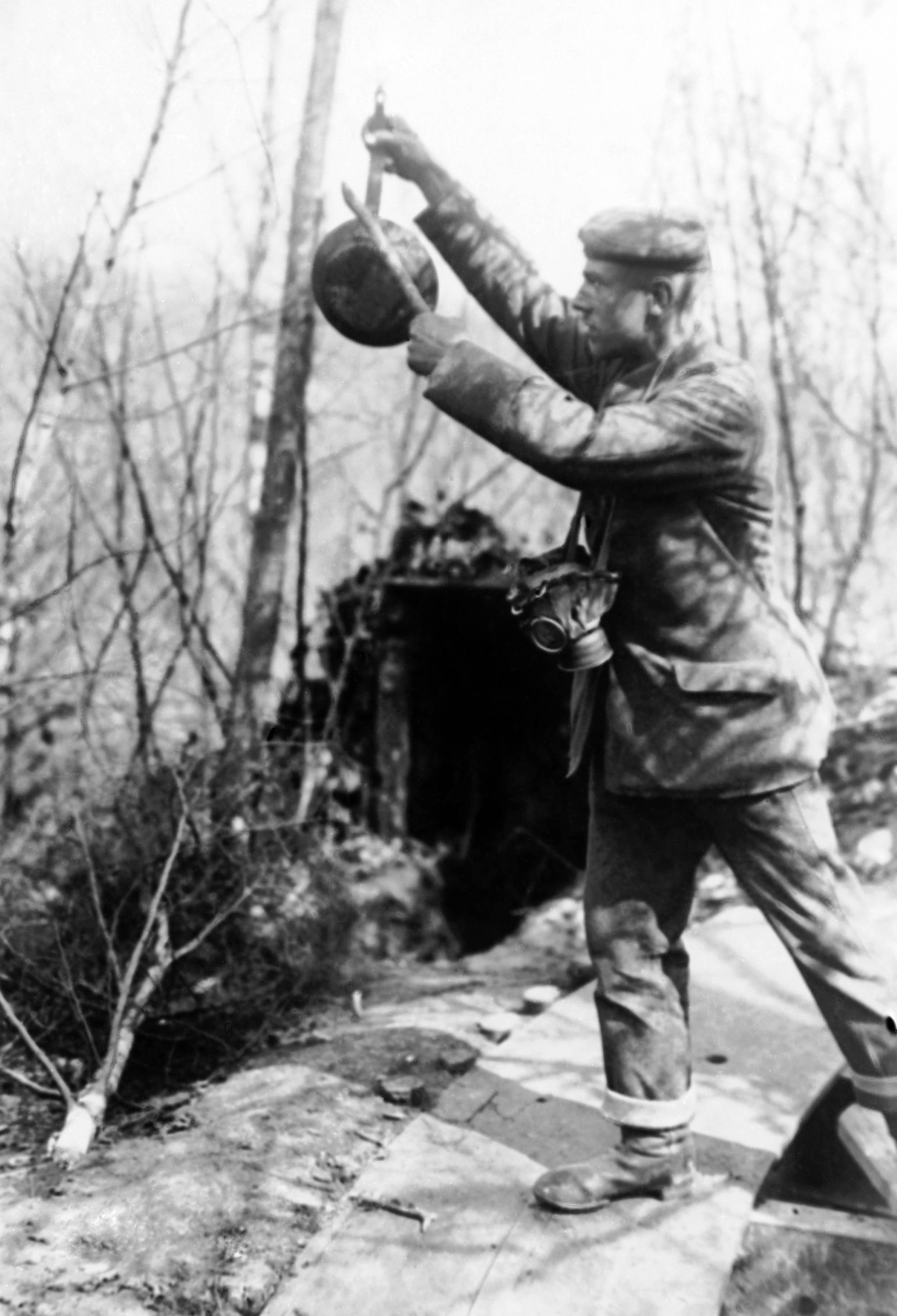 37 OF 100: In this undated file photo, an unidentified soldier, wearing a gas mask around his neck, bangs on a frying pan as a gas warning on the field near Reims, France.
