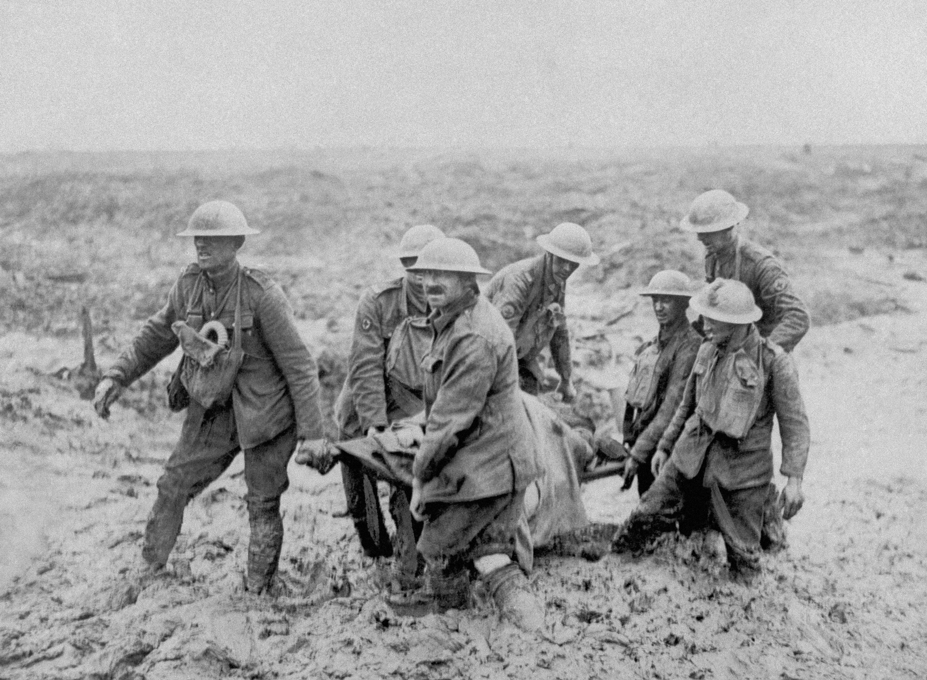 63 OF 100: In this 1917 file photo, World War Ie Canadian soldiers carry a stretcher through the mud near Boesinghe, Belgium.