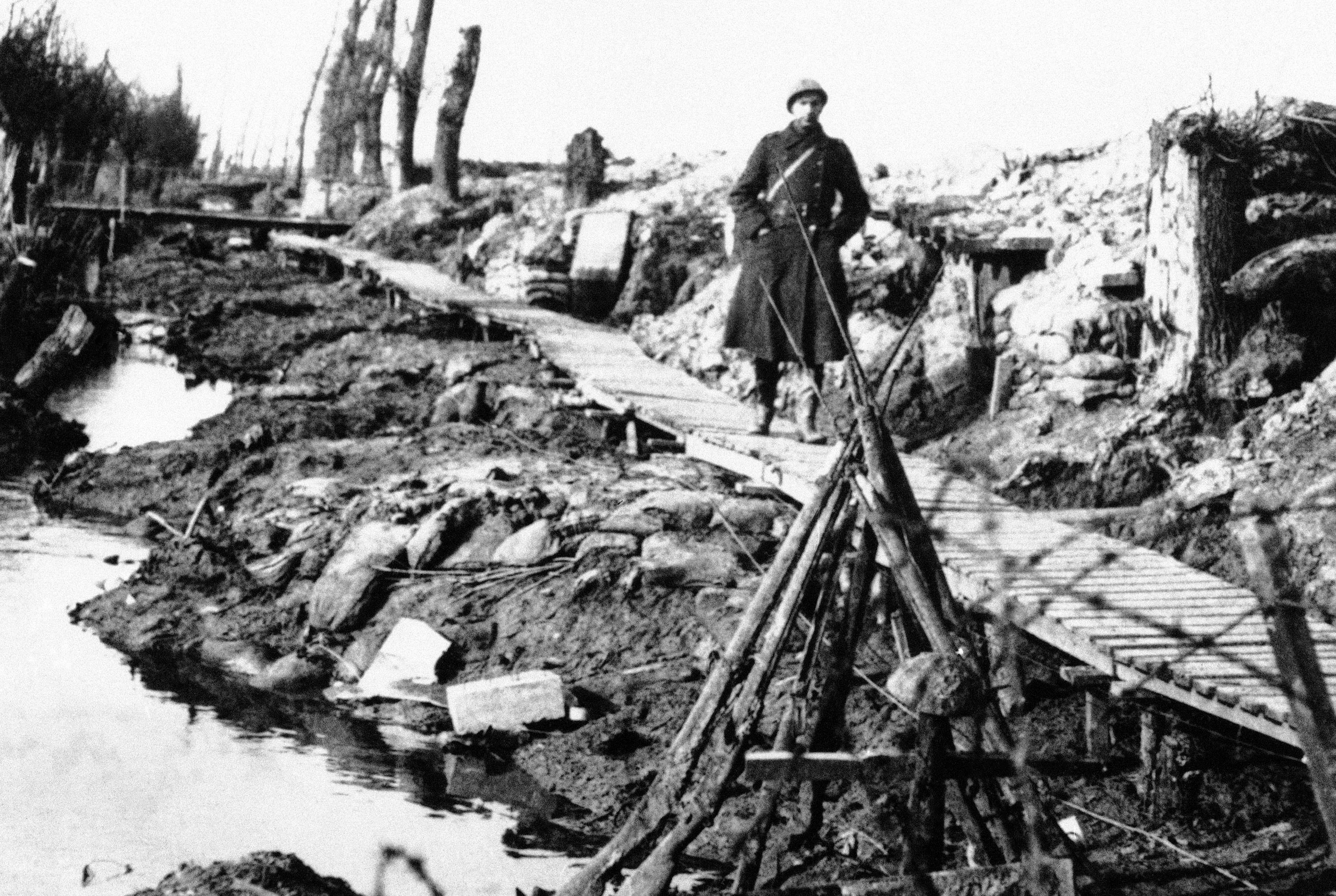 65 OF 100: In this 1917 file photo, an unidentified World War I soldier walks along wooden planks placed over the mud of Flanders' Fields near the Yperlee Canal near Ypres, Belgium.