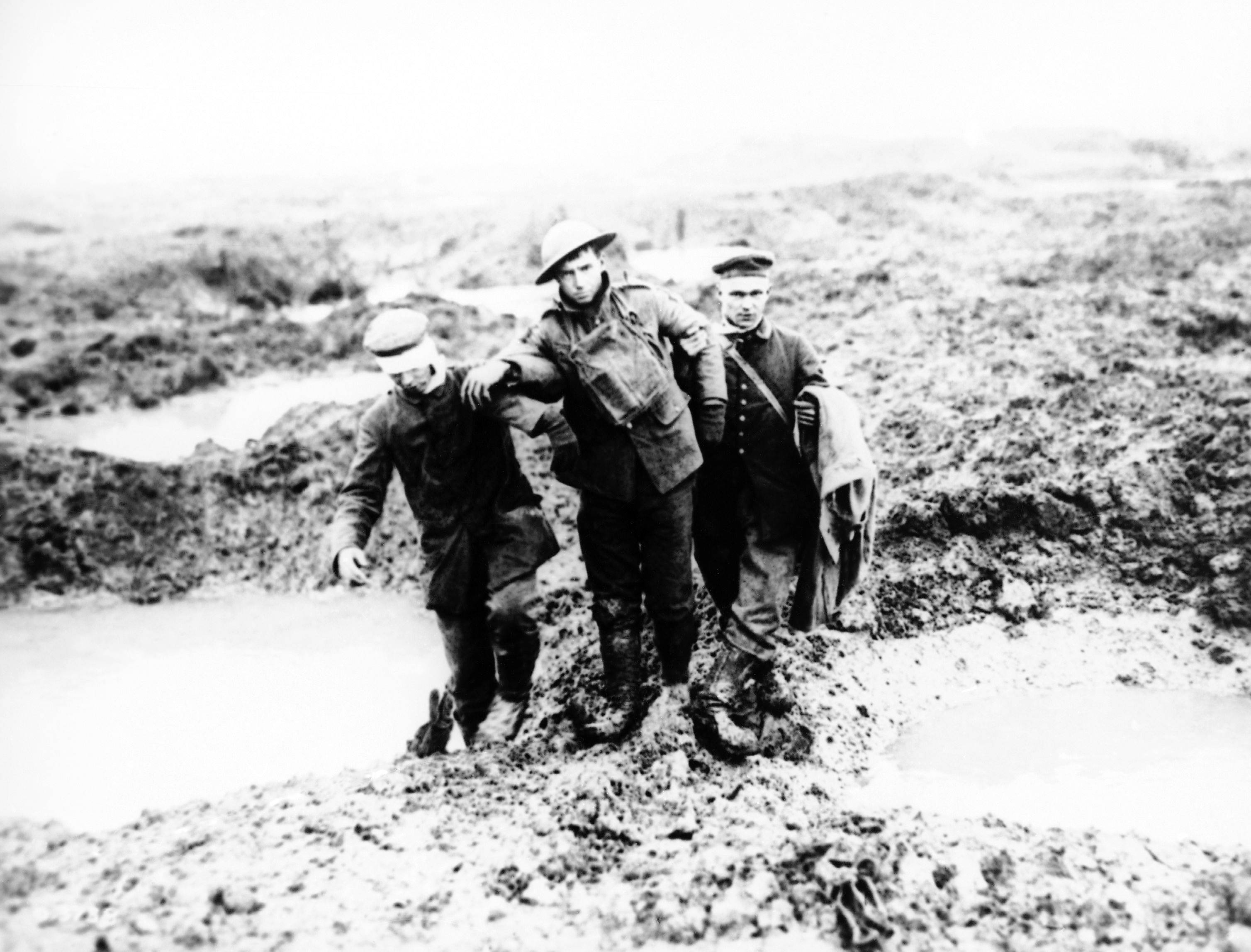 68 OF 100: In this 1917 file photo, wounded Canadian and German World War I soldiers help one another through the mud during the Battle of Passchendaele in Passchendaele, Belgium.