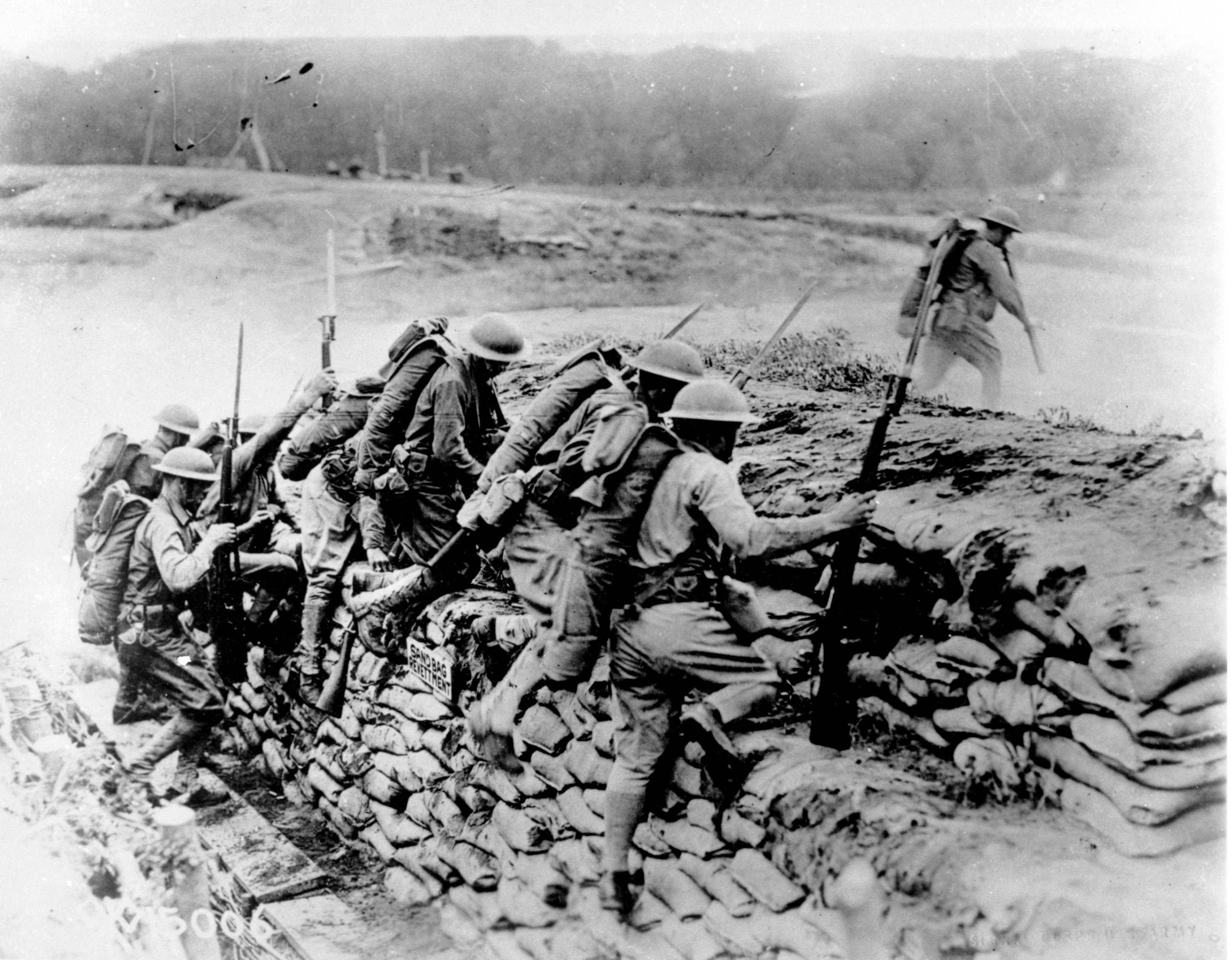 89 OF 100: In this 1918 file photo, American troops carrying guns with fixed bayonets climb over a sandbag revetment in France during World War I.