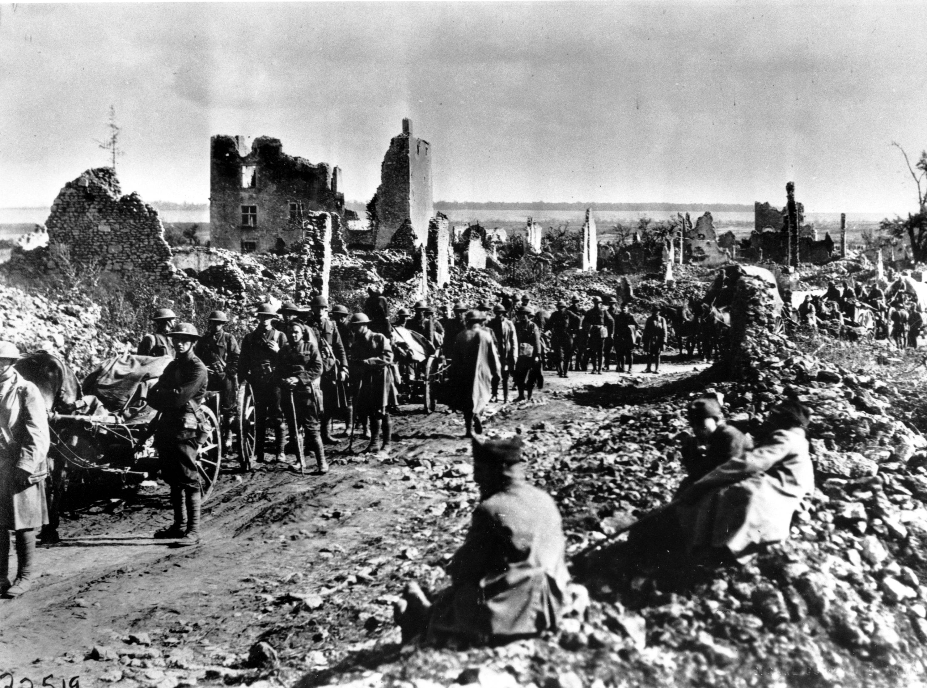 92 OF 100: In this July 1918 file photo, American troops from the 18th Infantry, First Division, pause in a ruined French town near St. Mihiel, France, during World War I.