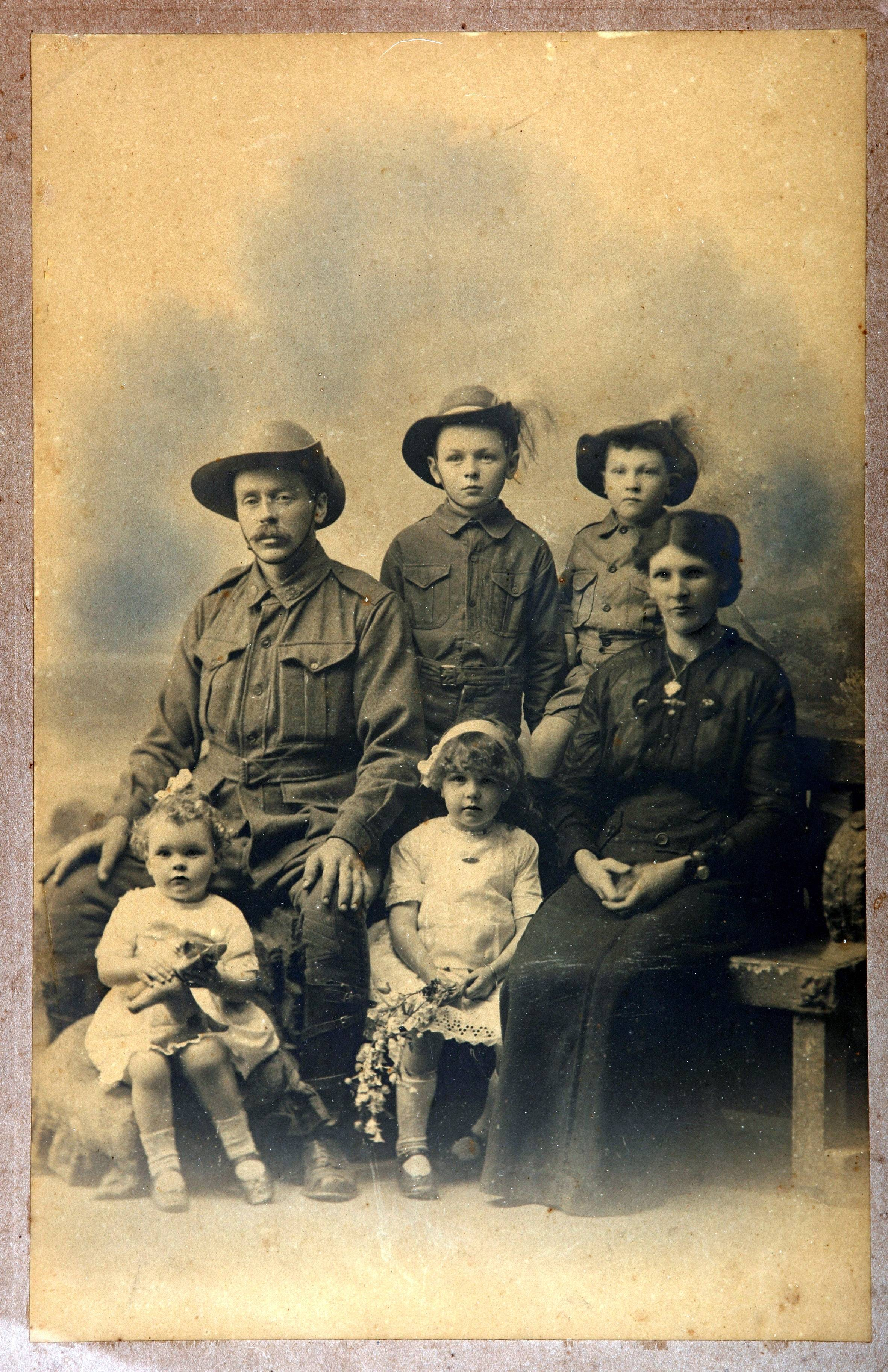 In this undated photo provided by the family, Australian soldier Andrew Bayne, rear left, poses with his wife and children in Brisbane, Australia, before leaving for the Western Front. Andrew Bayne, along with his brothers, enlisted for service in World War I. Andrew Bayne's journey took him to the battlefields of Bullecourt, Wytschaete, and Ypres before he was killed in action near Messines Ridge, Belgium on Aug. 19, 1917.