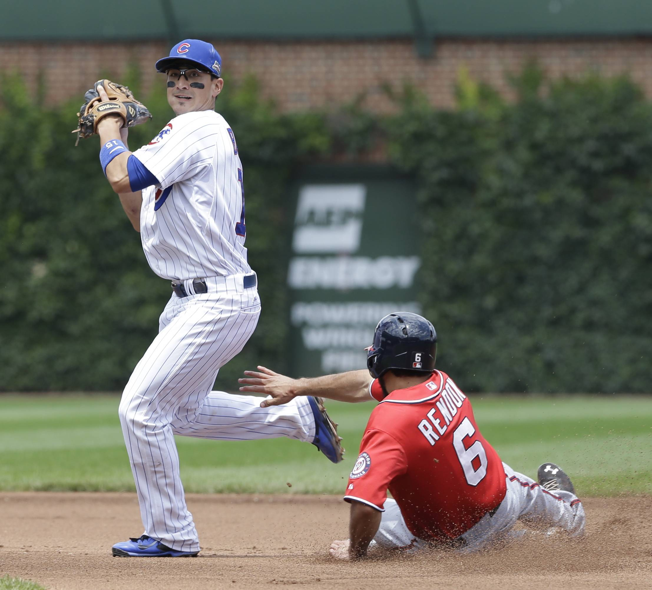 Darwin Barney, left, looks to first after forcing out Washington's Anthony Rendon at Wrigley Field on Saturday.