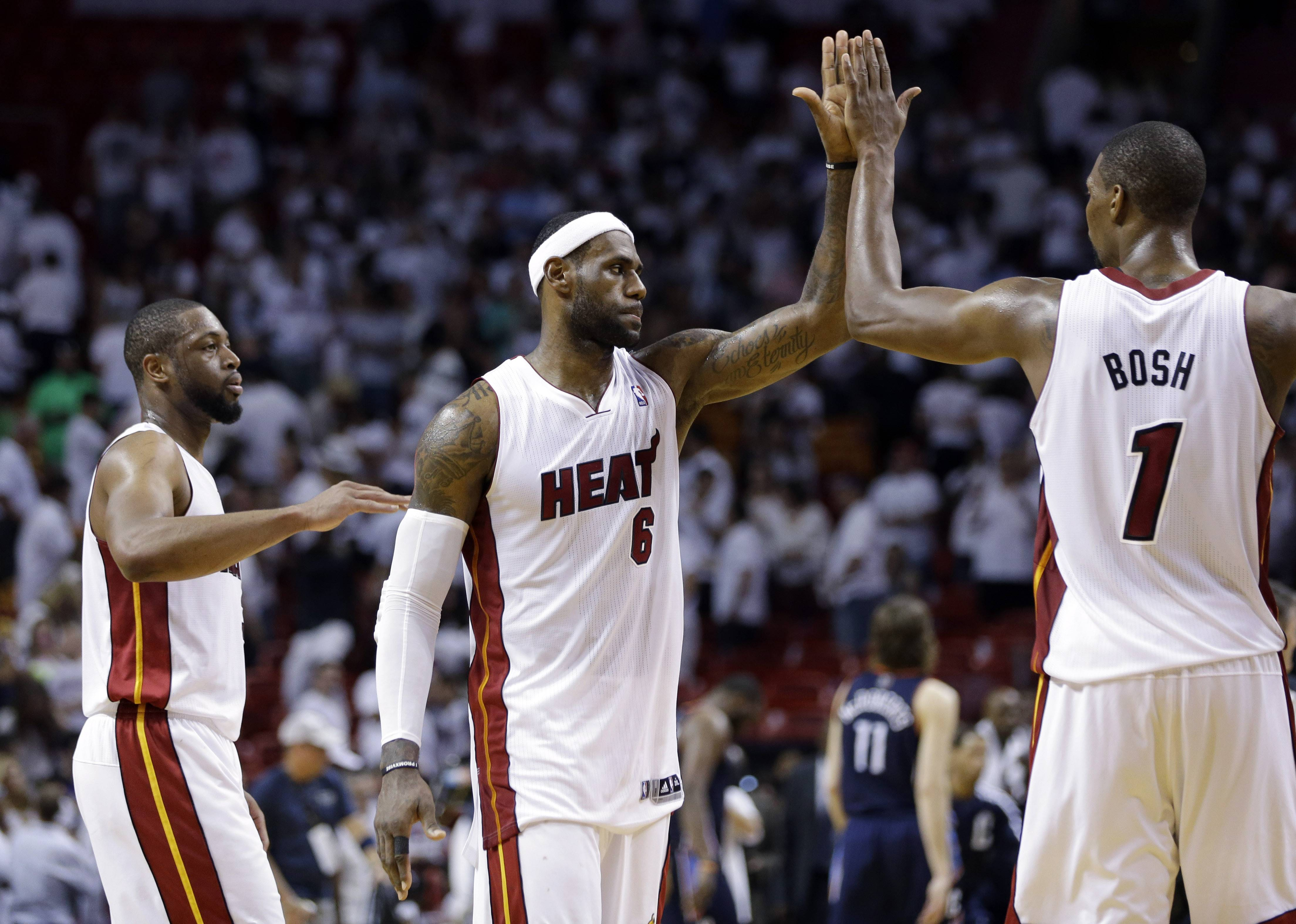 FILE - In this April 23, 2014 file photo, Miami Heat's LeBron James (6) high-fives Chris Bosh (1) after the Heat defeated the Charlotte Bobcats 101-97 in Game 2 of an opening-round NBA basketball playoff series in Miami. At left is Dwyane Wade. A person familiar with the situation tells The Associated Press that James has decided to opt out of the final two years of his contract with the Heat and become a free agent on July 1. Opting out does not mean James has decided to leave the Heat, said the person, who spoke on condition of anonymity because neither the four-time NBA MVP nor the team had made any public announcement.