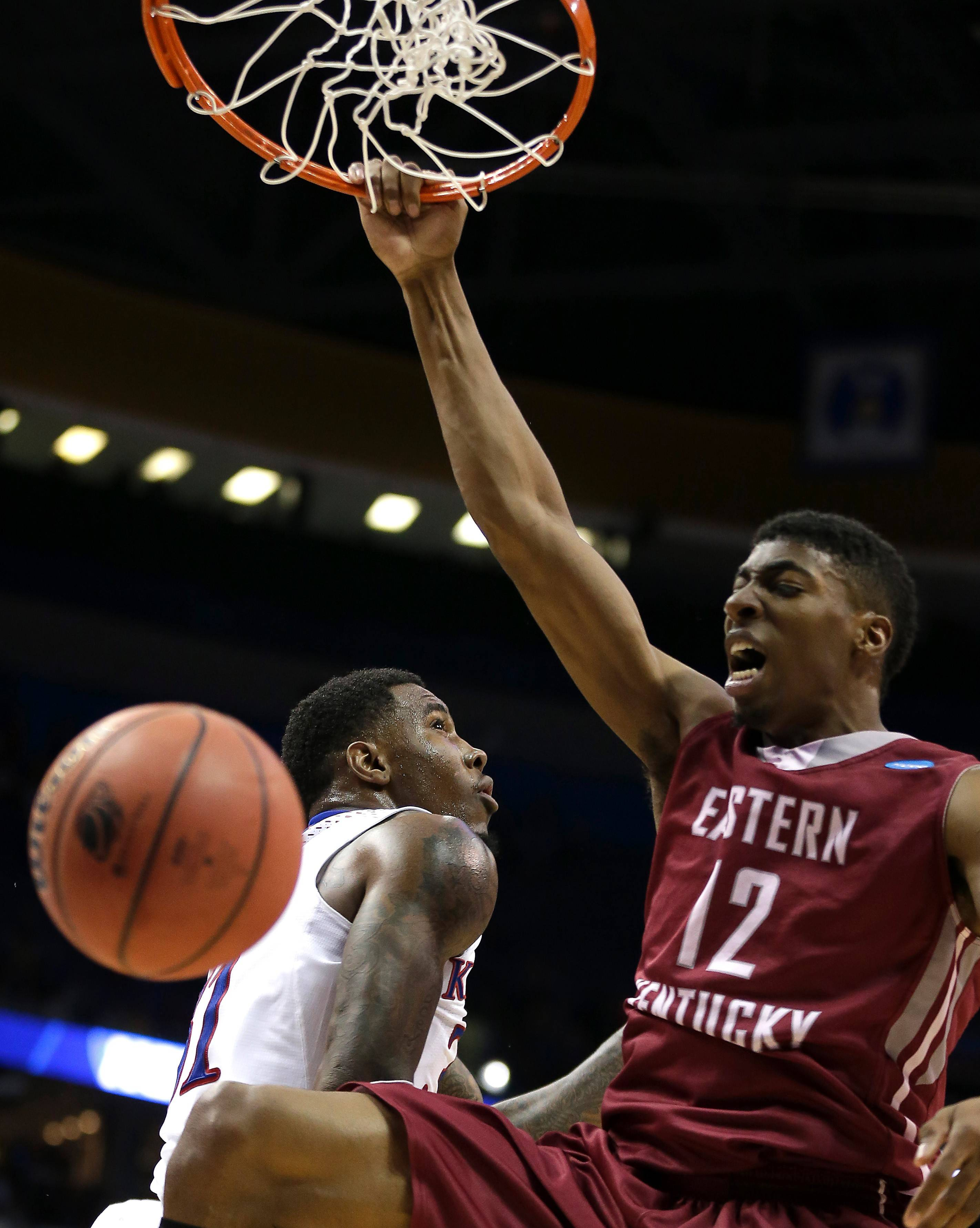Eastern Kentucky's Marcus Lewis (12) gets past Kansas' Jamari Traylor to dunk the ball during the second half of a second-round game in the NCAA college basketball tournament March 21 in St. Louis. Kansas won the game 80-69.