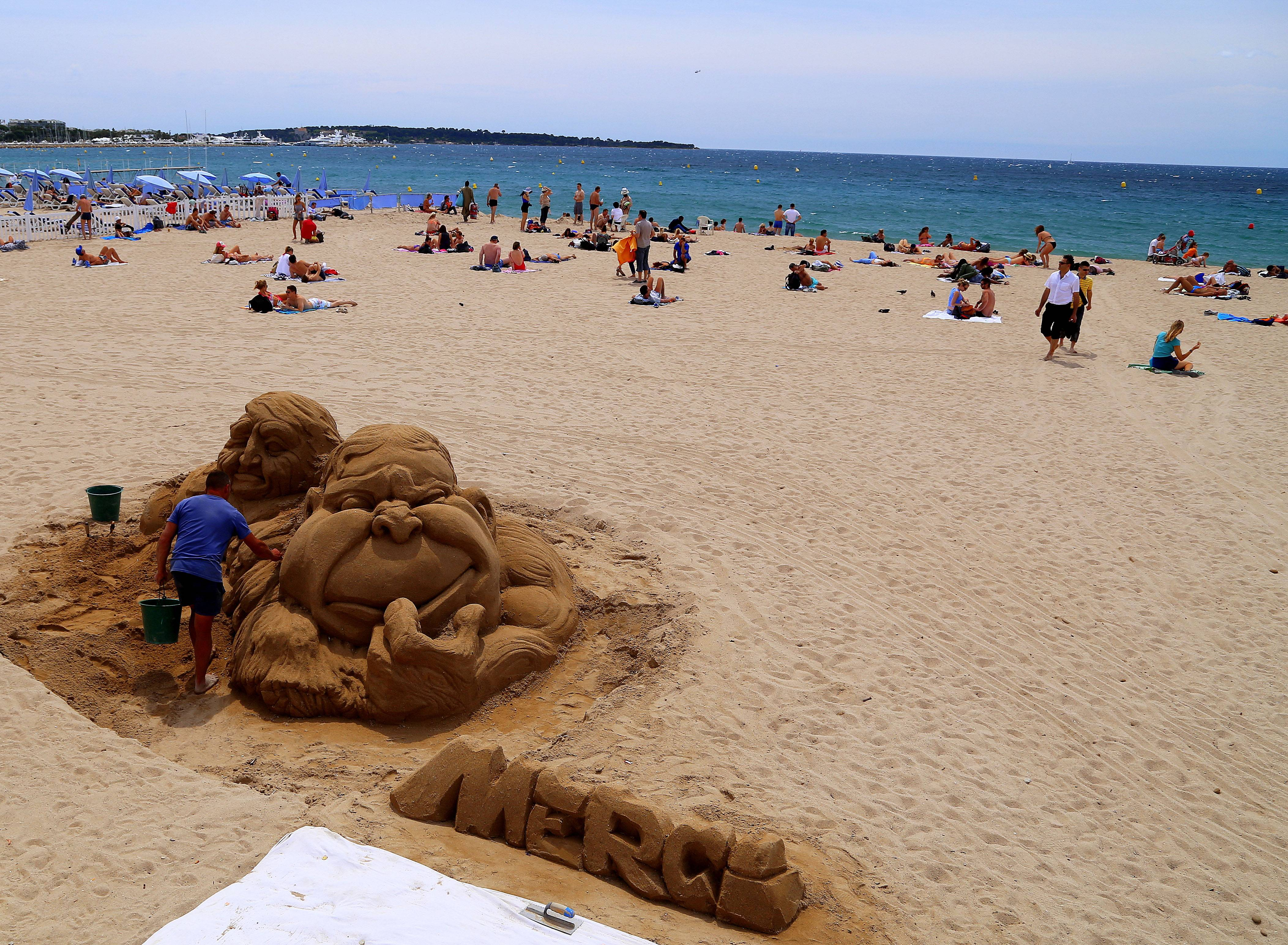 A man works on a sand sculpture on a free beach in Cannes, one of several free attractions in this Riviera resort. Cannes is a favorite destination for the wealthy, but the Riviera resort also offers plenty of simple, inexpensive pleasures, from the beach to street strolls.
