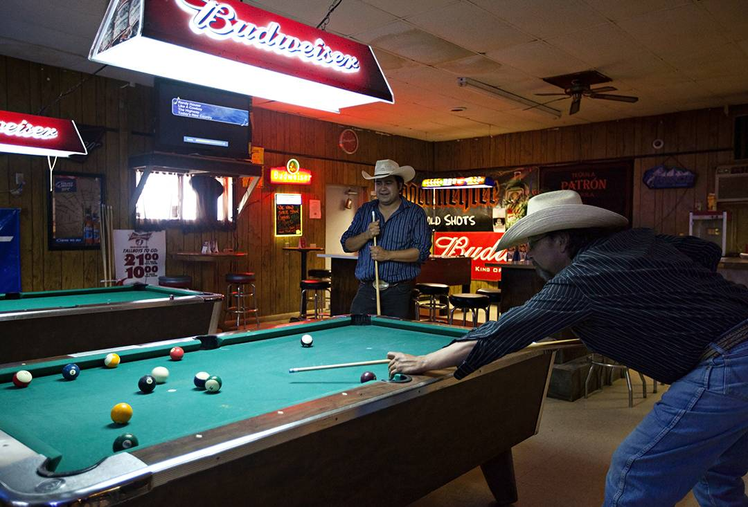 Ray Runnels, right, and his son Ray Runnels Jr. shoot pool at Swett Tavern in Swett, S.D. The unicorporated town of Swett is owned by one person who has put it up for sale.