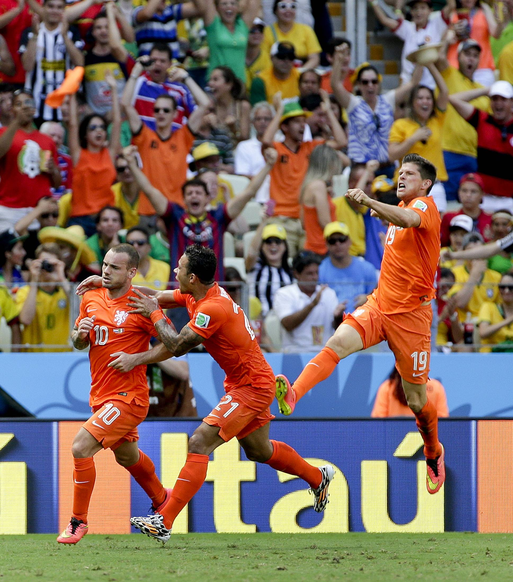 The Netherlands' Wesley Sneijder (10) celebrates with teammates Memphis Depay and Klaas-Jan Huntelaar (19) after scoring his side's first goal during the World Cup round of 16 soccer match between the Netherlands and Mexico at the Arena Castelao in Fortaleza, Brazil, Sunday, June 29, 2014.