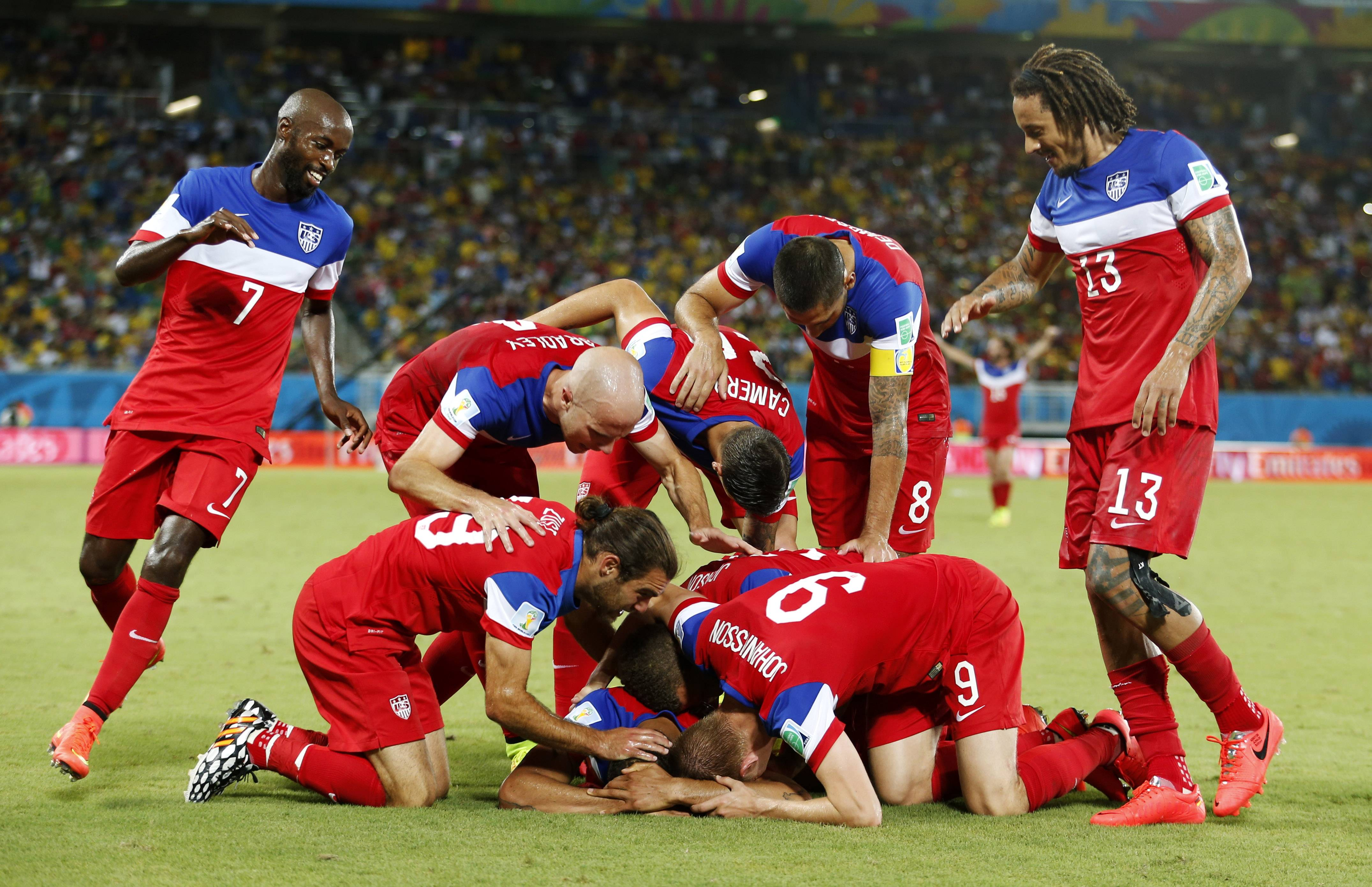 The United States team surrounds John Brooks after he scored his side's second goal to defeat Ghana 2-1 during the group G World Cup soccer match between Ghana and the United States at the Arena das Dunas in Natal, Brazil, June 16. The U.S. team is now readying for Tuesday's matchup against Belgium.