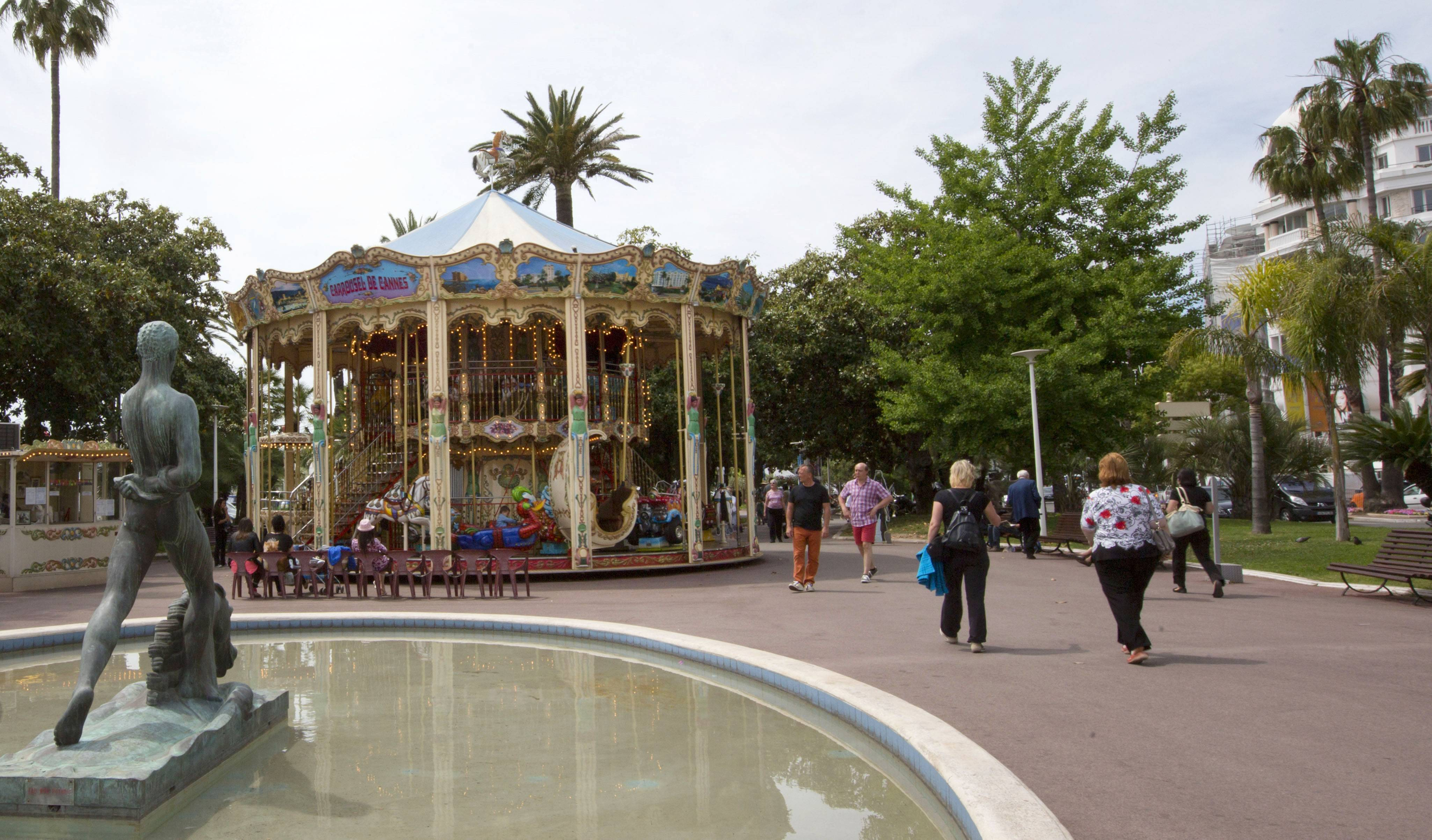 People walk in a park near a carousel in Cannes, southern France.