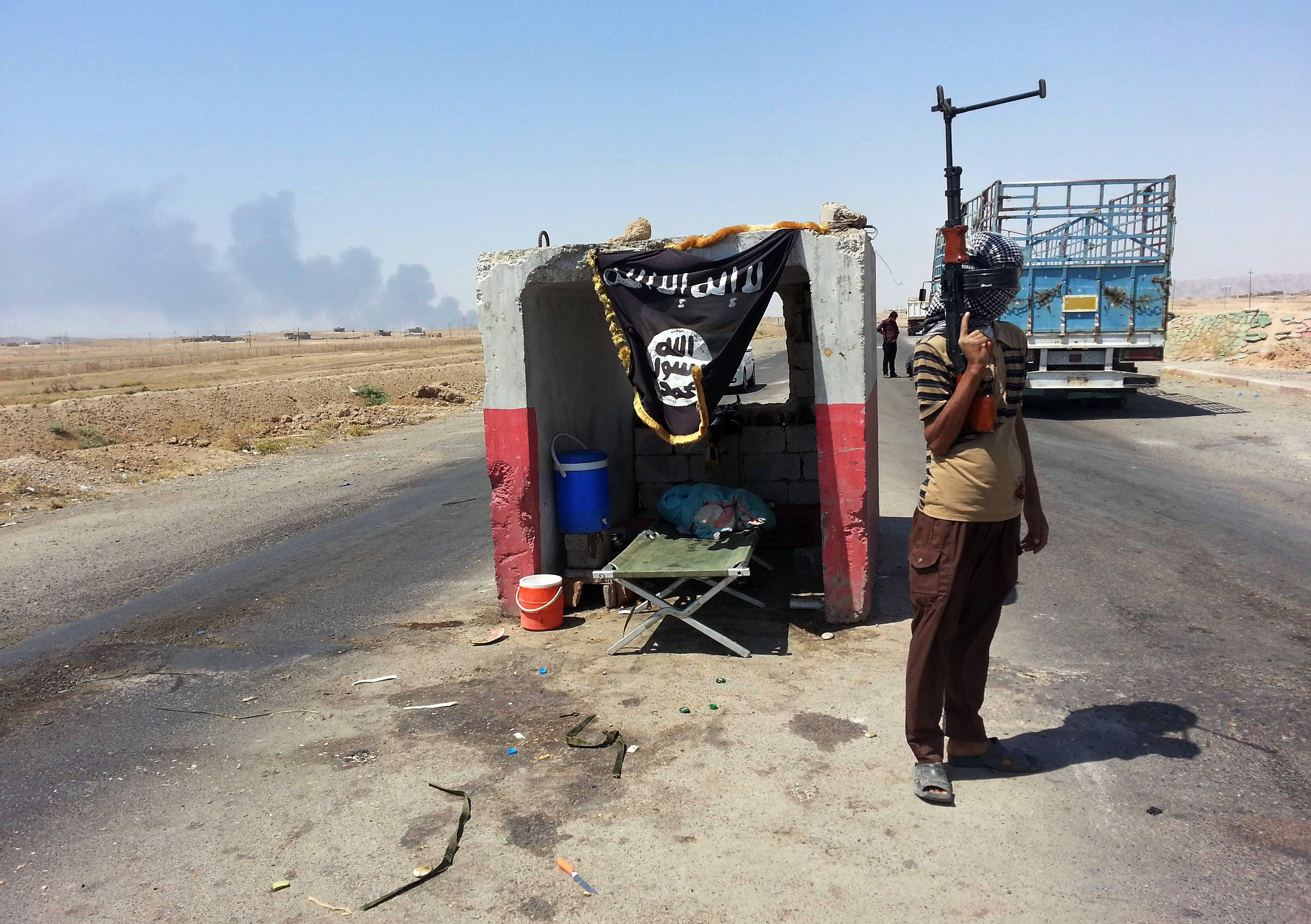 An al-Qaida-inspired militant stands guard at a checkpoint captured from the Iraqi Army some 155 miles north of Baghdad June 19. The al-Qaida breakaway group formally declared the creation of an Islamic state on Sunday in the territory under its control.