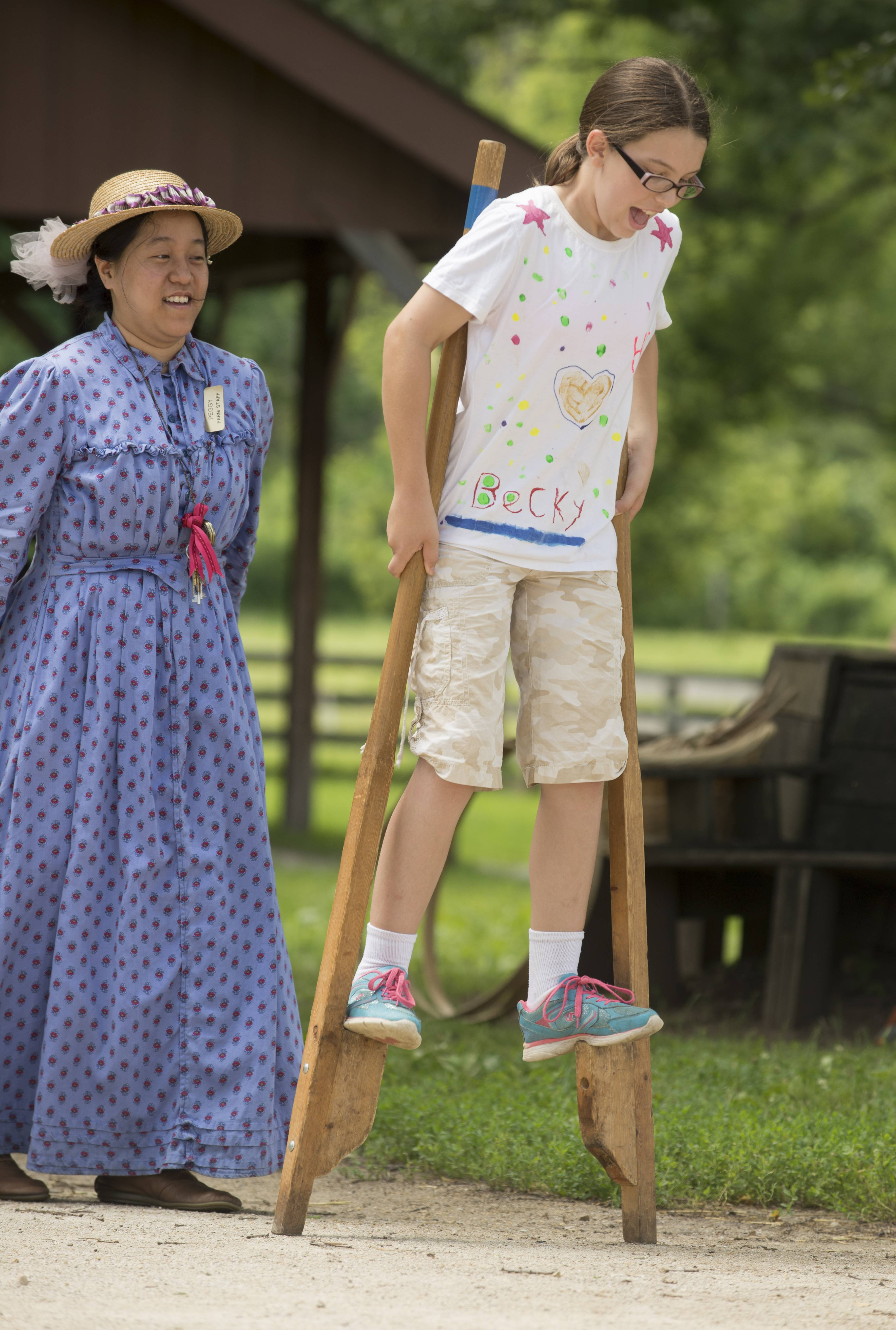 Seasonal staff member Peggy Kuo watches as Becky Reidy, 10, of Roselle tries out a pair of stilts Sunday during Kline Creek Farm's old-fashioned 4th of July celebration.