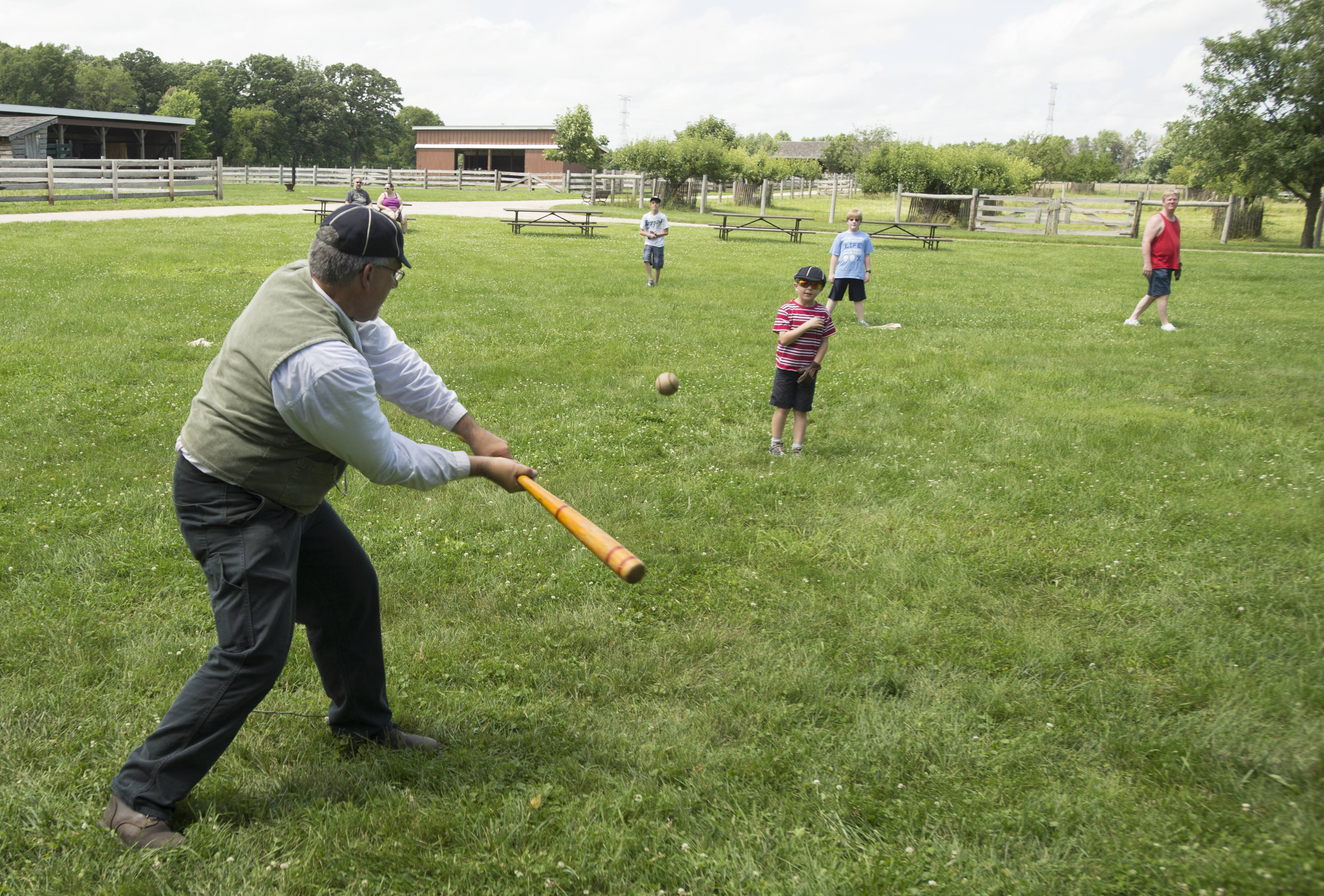 Children play old-fashioned baseball Sunday during Kline Creek Farm's 4th of July celebration.