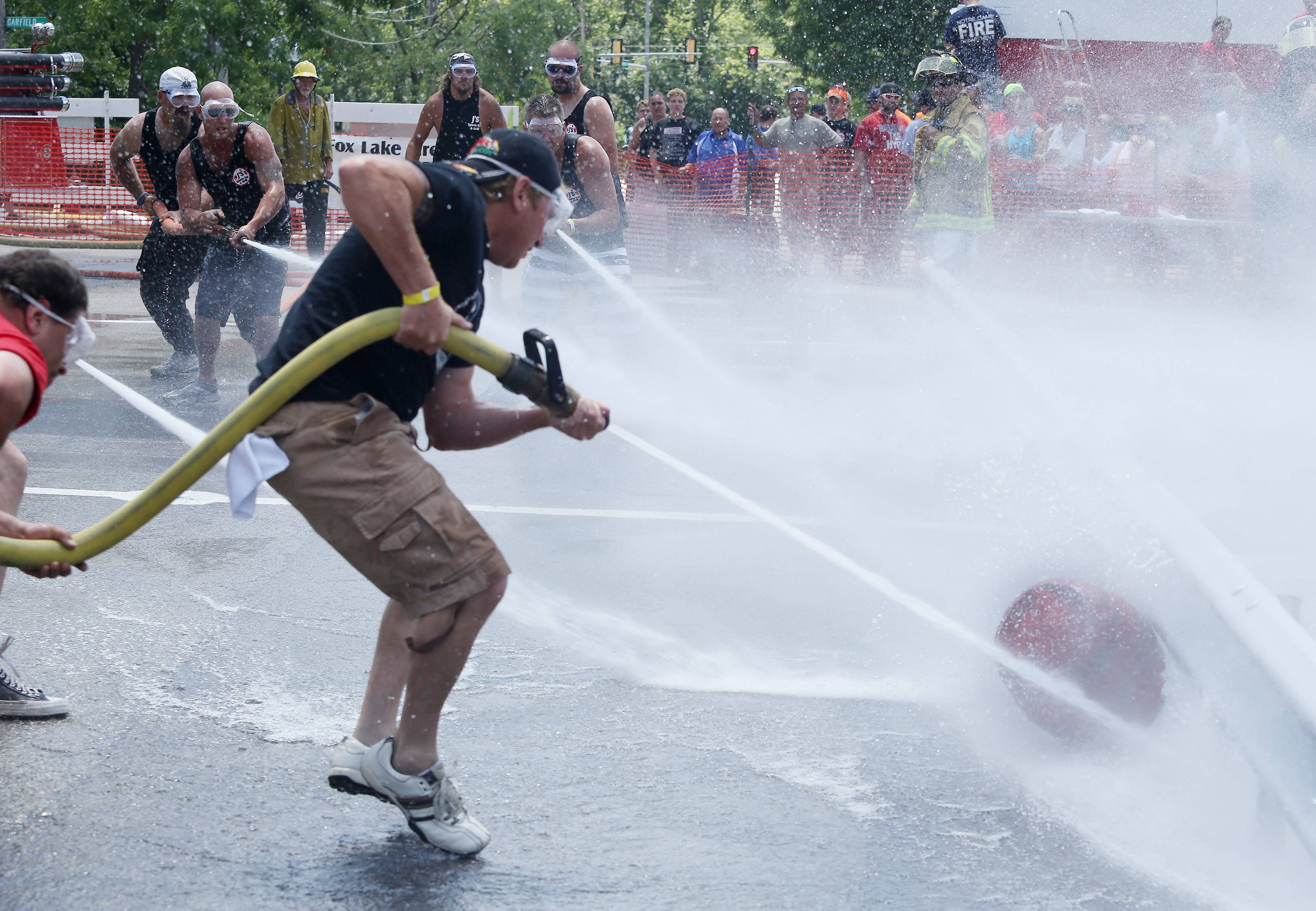 Eric Sutton, center, of Bingo Bunnies tries to keep the keg from coming at him as J's Sports Bar advances during the water fights Sunday at the Fox Lake Firemen's Fest. Teams representing area businesses and other groups competed using high-powered water hoses to blast a keg across the opponent's line.