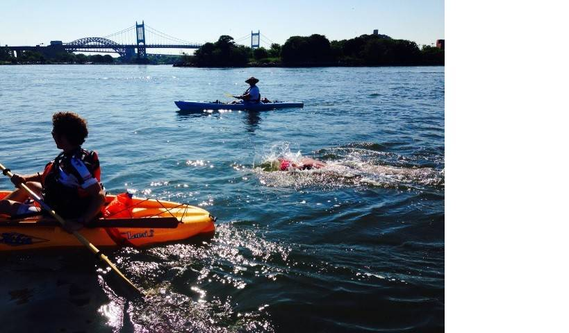 Doug McConnell, 56, of Barrington swims 28.5 miles around Manhattan Island Saturday while his good friend Master Swimmer Don Macdonald, 52, of Barrington tracks his progress in the kayak in the distance. Both made it the distance.