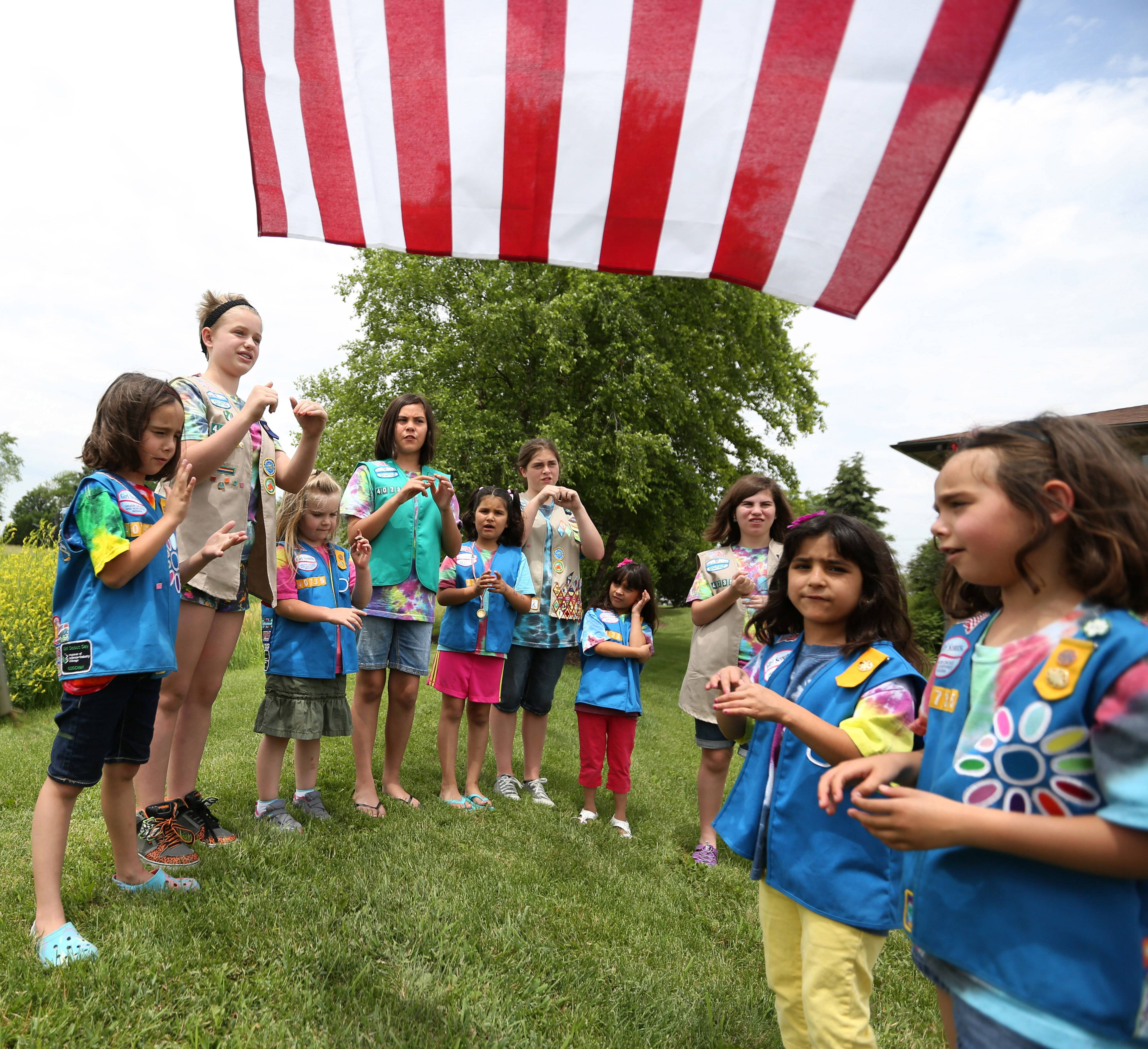 Members of Girl Scout Troop 40735, designed for the deaf and hard of hearing, sign the Pledge of Allegiance near a U.S. flag at recent meeting in the Mundelein area. Girls travel from as far as Blue Island to attend Troop 40735's meetings.