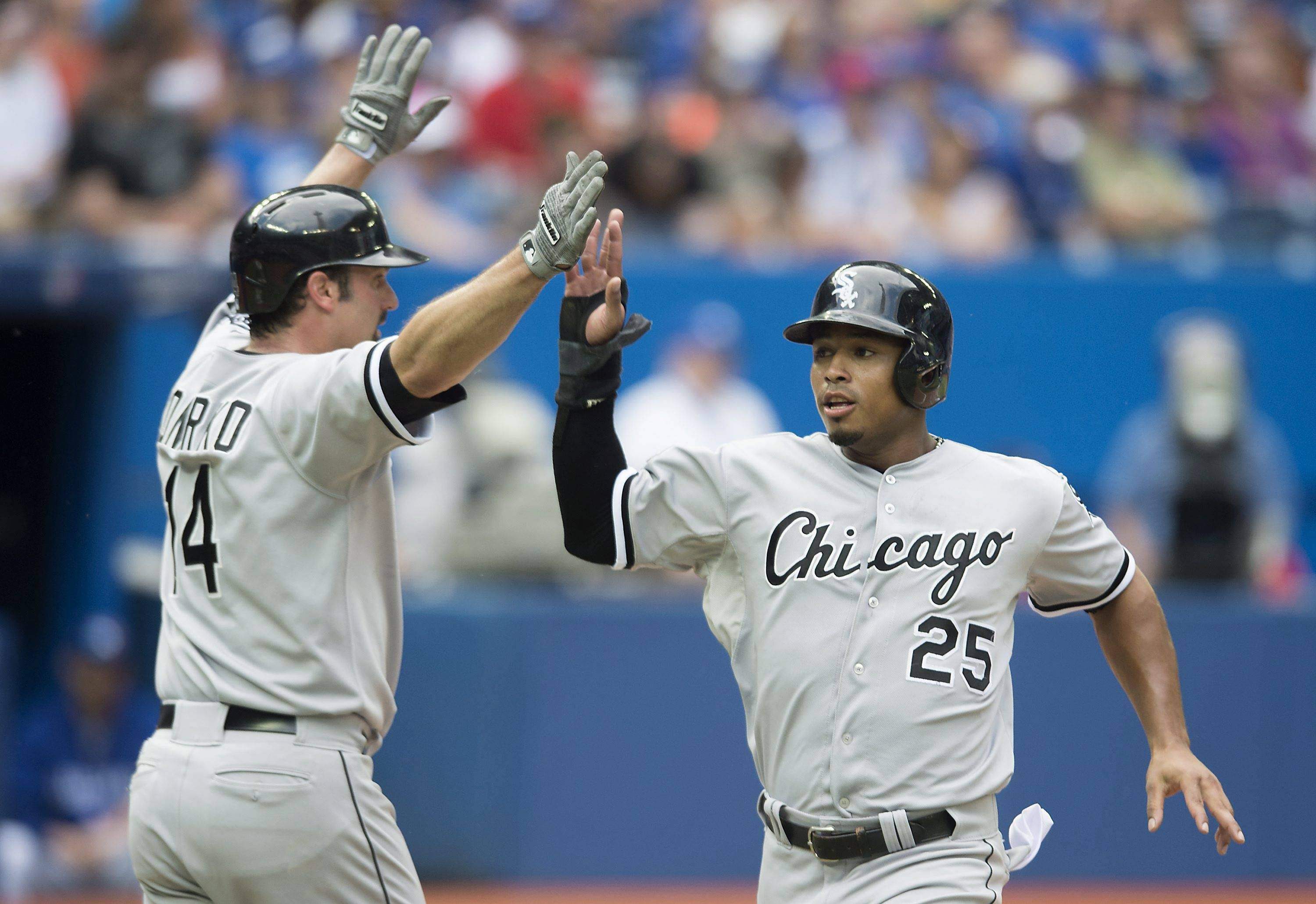 Chicago White Sox's Moises Sierra, right, celebrates with teammate Paul Konerko after scoring on a two-run single by Tyler Flowers in the ninth inning of a baseball game against the Toronto Blue Jays in Toronto, on Sunday, June 29, 2014. Chicago won 4-0.