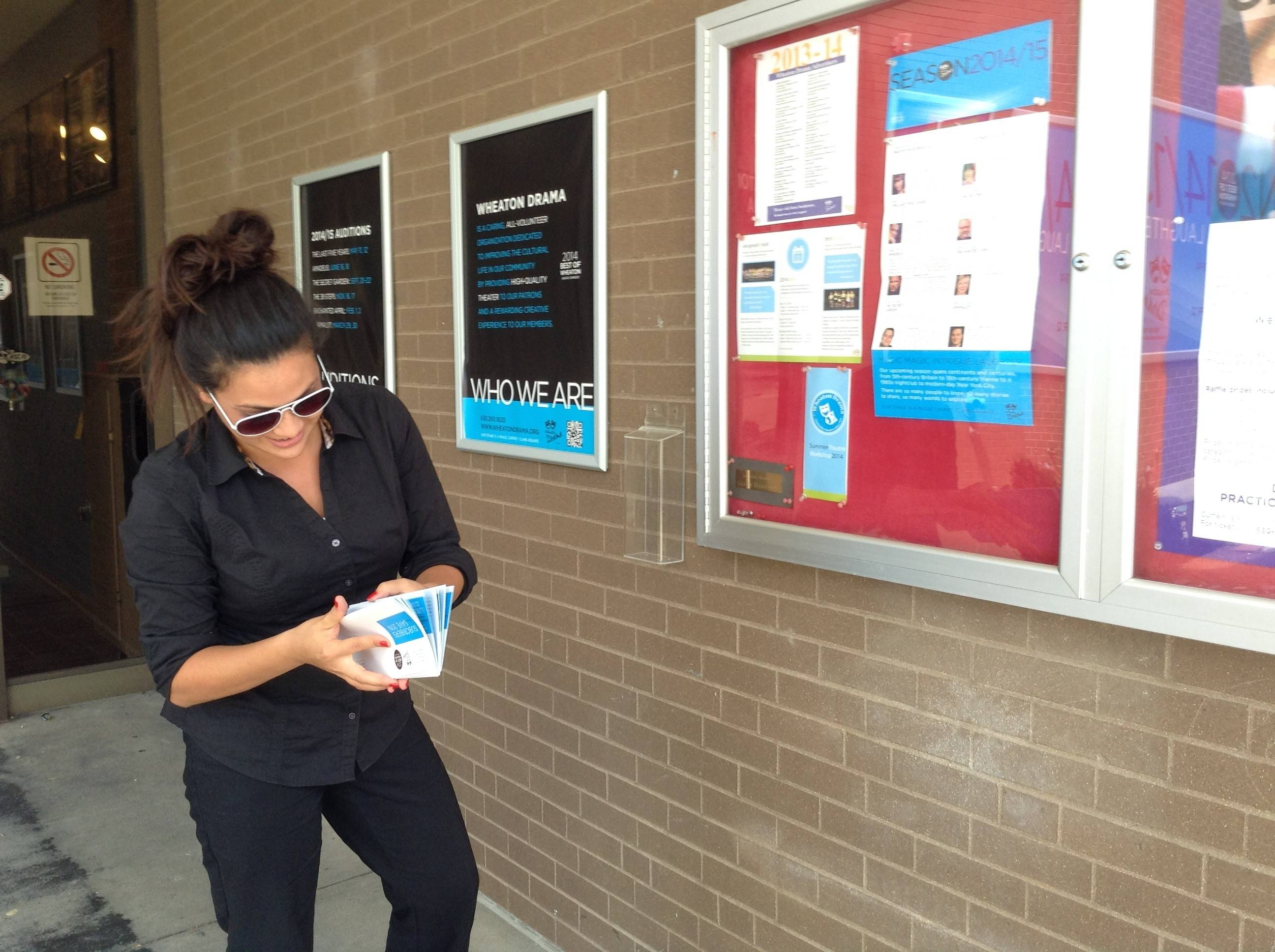 "Hilary Dyer searches for a hidden envelope in front of the Wheaton Drama playhouse on June 26. The Downtown Wheaton Association and Ivy restaurant sponsored an inaugural ""Hidden Cash Dash"" last week by hiding six envelopes containing $40 cash and a $10 Downtown Wheaton gift certificate."