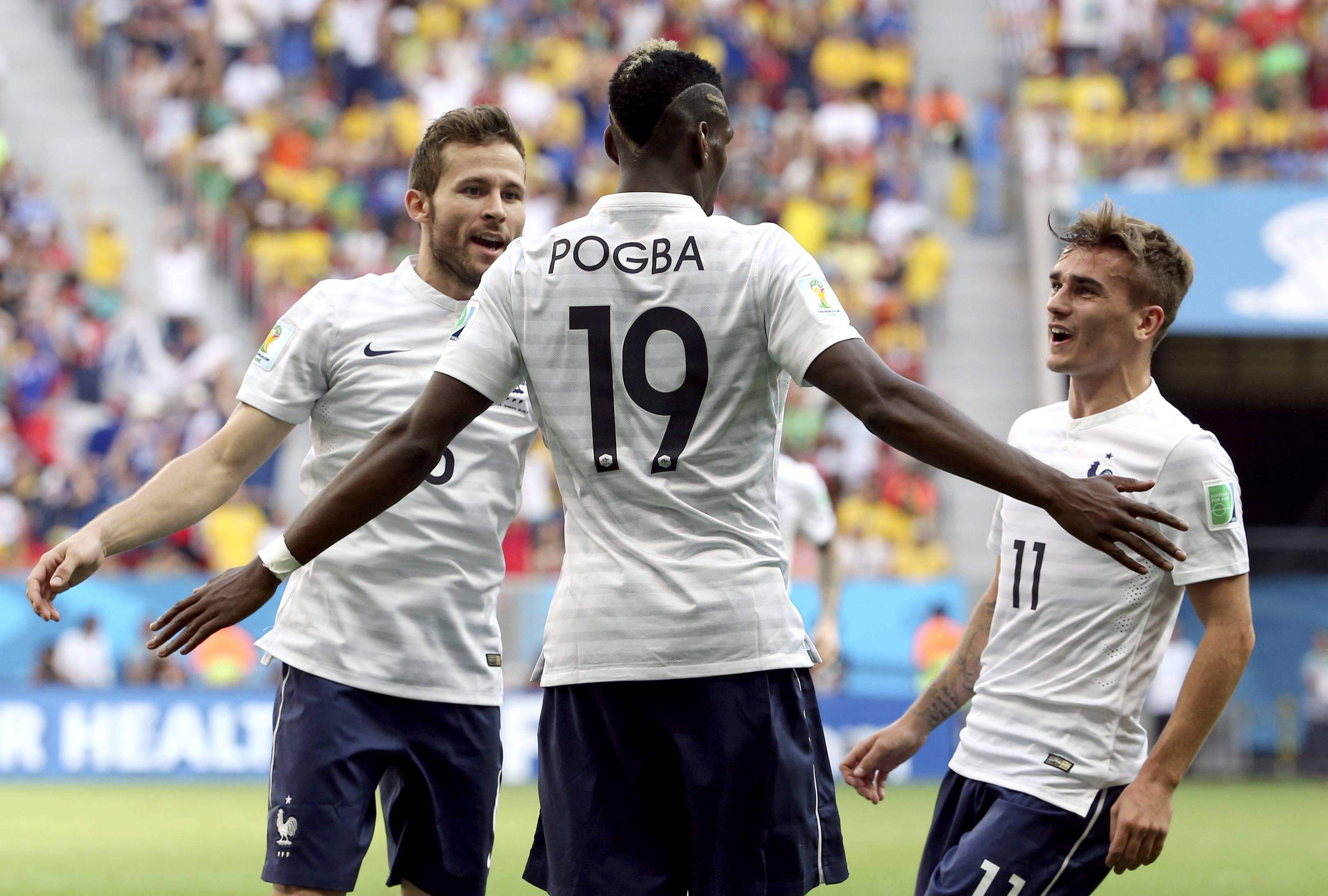 France's Paul Pogba (19) celebrates with teammates Yohan Cabaye, left, and Antoine Griezmann, right, Monday after scoring his side's opening goal during the World Cup round of 16 soccer match against Nigeria at the Estadio Nacional in Brasilia, Brazil.