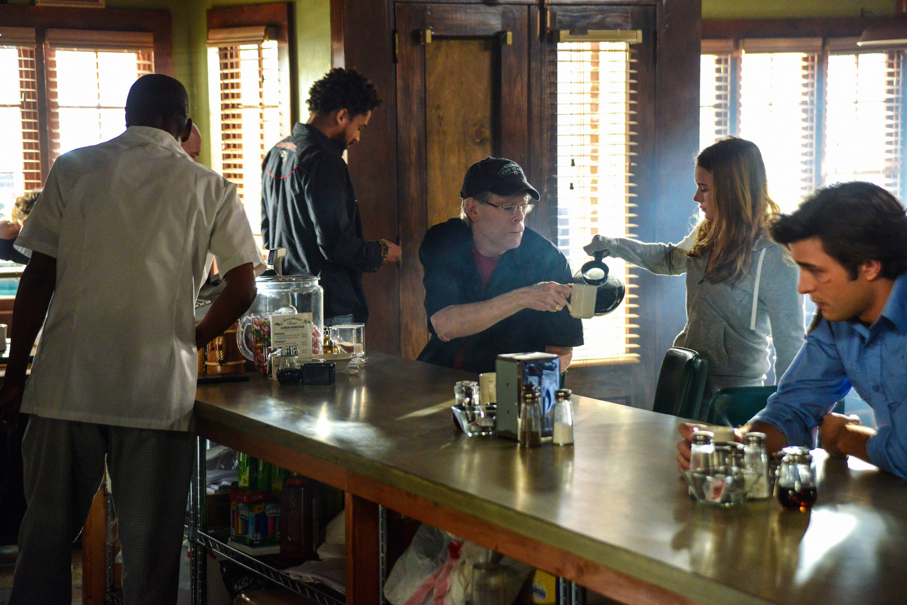 "Nicholas Strong, Stephen King, Britt Robertson and Alexander Koch in a scene from the episode ""Heads Will Roll,"" the second season premiere of ""Under the Dome."""