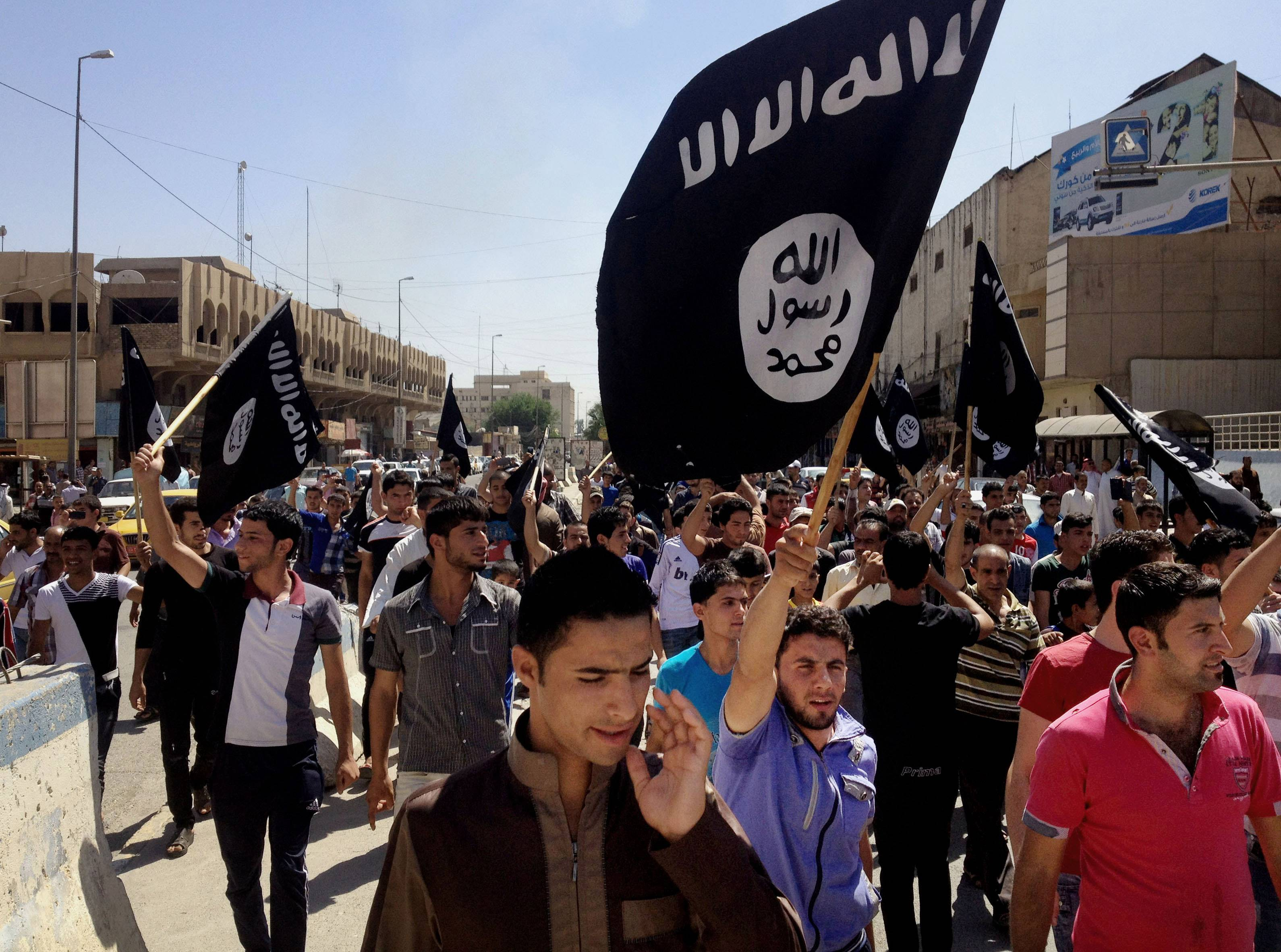 Demonstrators chant slogans to support al-Qaida-inspired Islamic State of Iraq and the Levant as they carry al-Qaida flags in front of the provincial government headquarters in Mosul, 225 miles northwest of Baghdad, Iraq, in this June 16, 2014, file photo.
