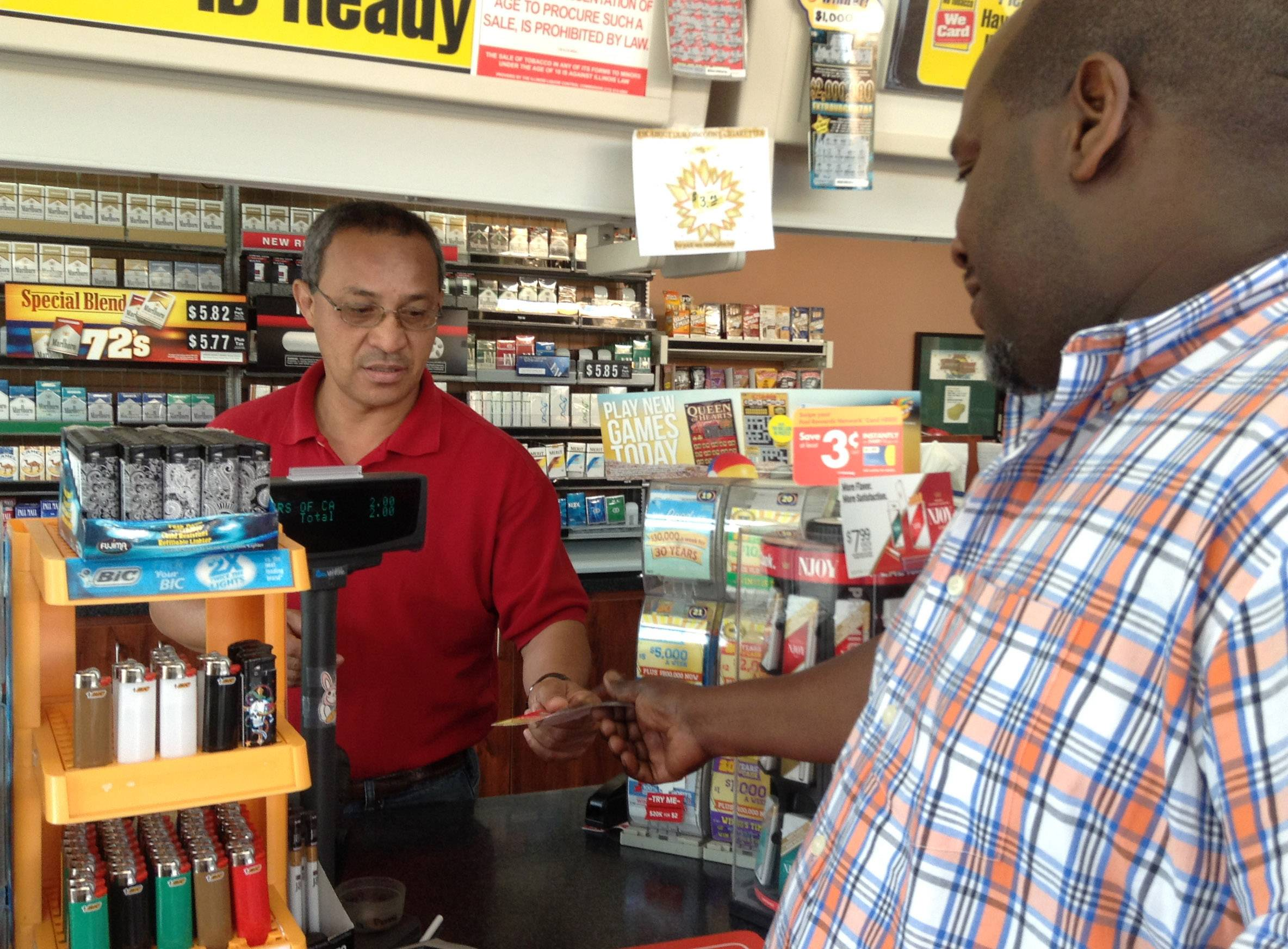 Otto Coleman, left, night shift clerk at Car Spa Shell in Libertyville, accepts a winning ticket from Mundelein resident Maurice Shoots.