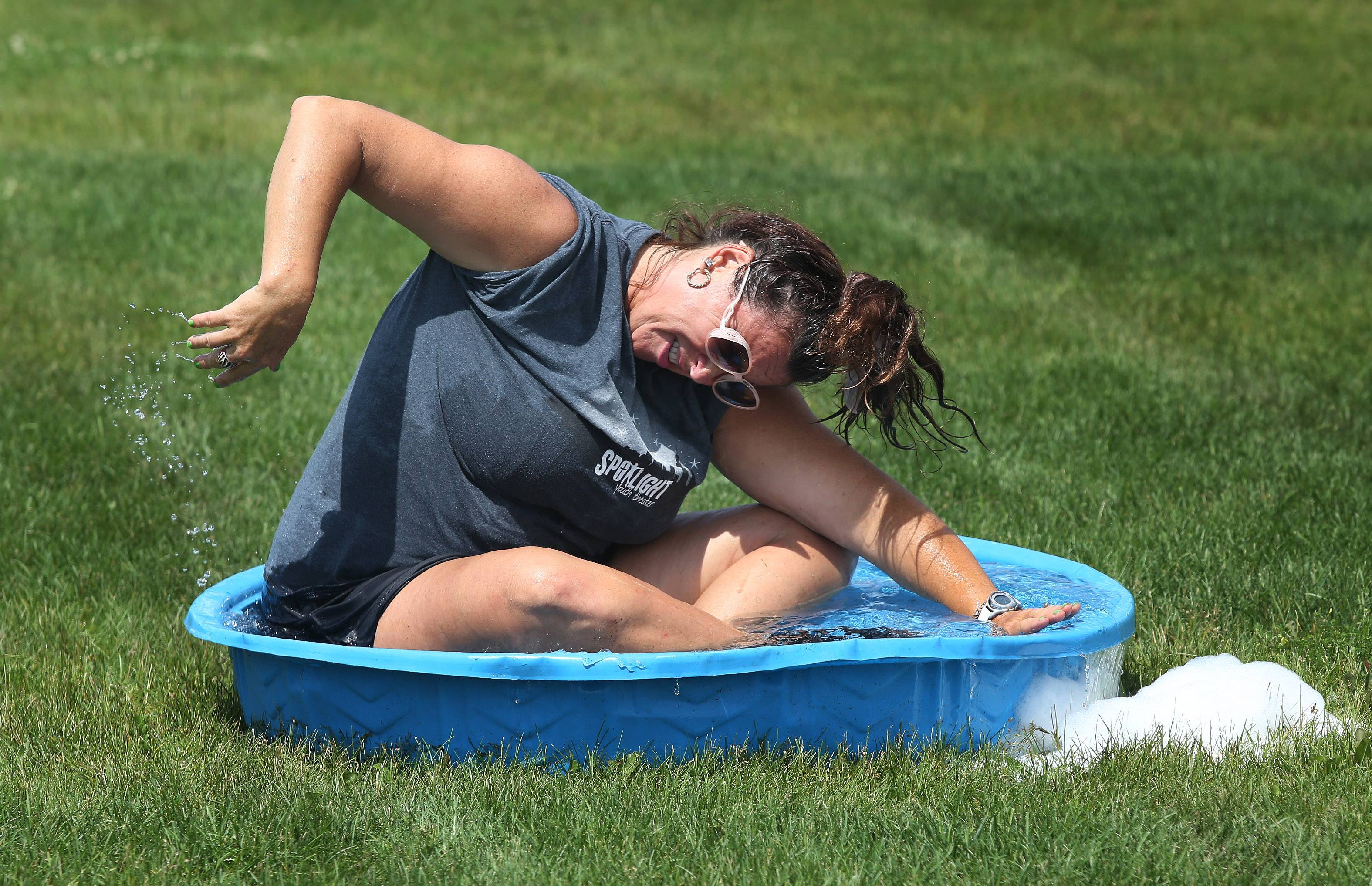 "Camp coordinator Michele Christensen swims in a kiddie pool during Wet Day at the Spotlight Youth Theater summer camp Tuesday at The Chapel in Libertyville. The week-long camp focuses on voice, drama and dance as they prepare for the presentation of ""Surfin' the High Seas"" on Friday."