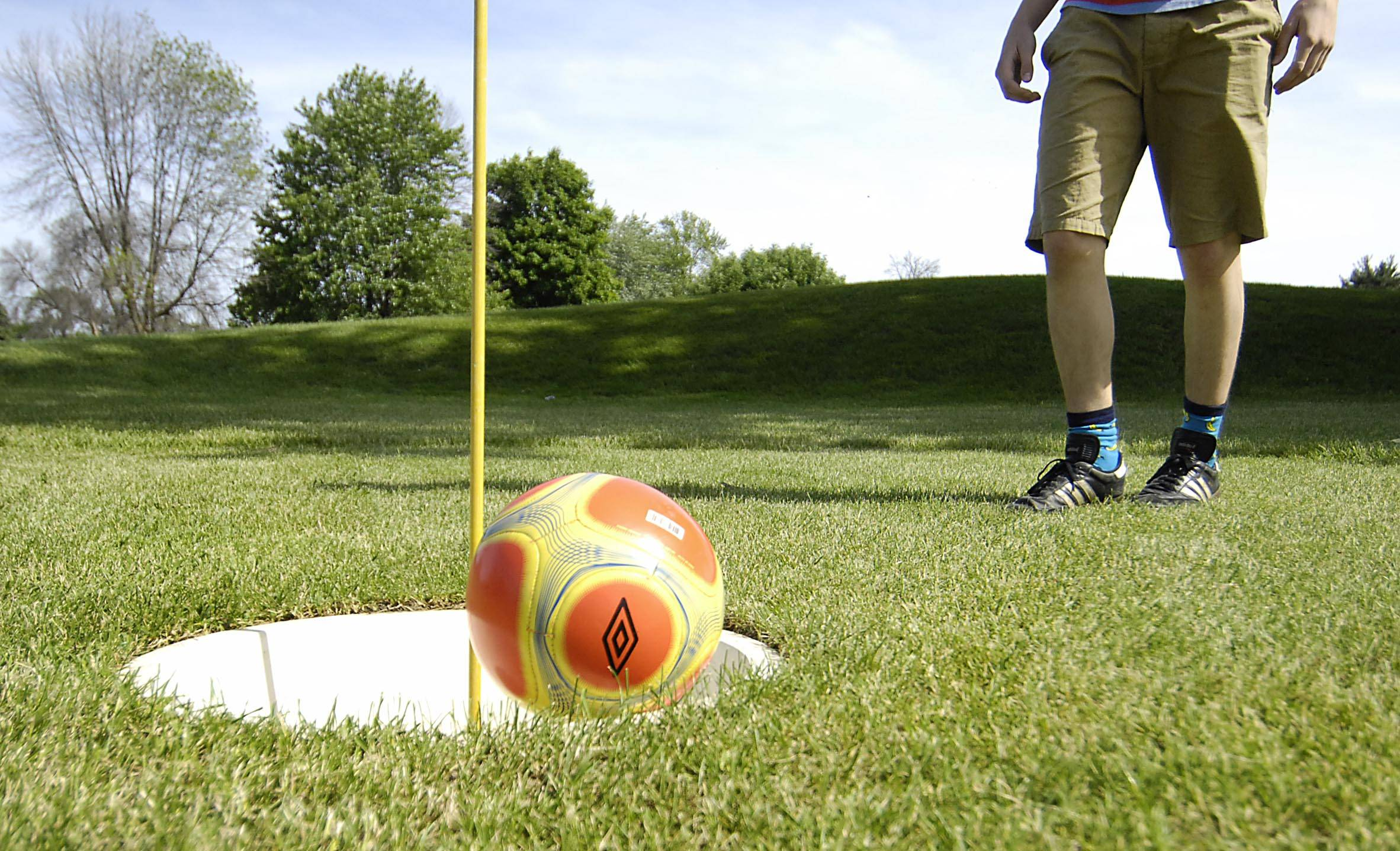 "Alex Lenski, 16, of Geneva, rims his soccer ball around the 20"" cup as he plays footgolf at Bonnie Dundee Golf Club in West Dundee Sunday."