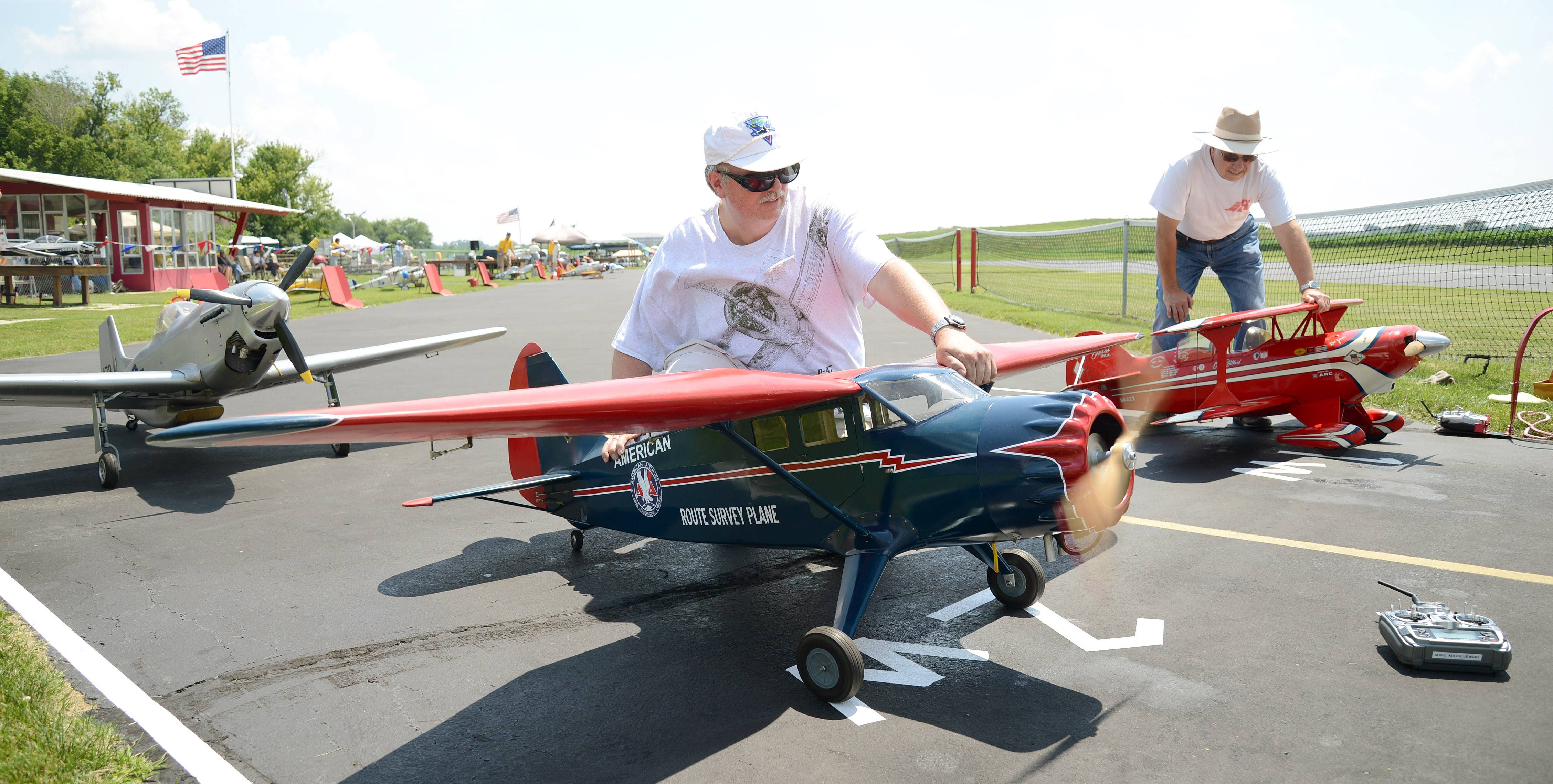 Mike Maciejewski, of St. Charles, hangs onto his Stintson Reliant R9 plane as the engine warms up, readying for take off, at the Fox Valley Aero Club's Windy City Warbird and Classics model airplane show in St. Charles on Friday. Maciejewski a member of the Surburban R.C. Barnstormers, Inc. model airplane flying club for about 30 years, often flying at Fox Valley Aero Club events.