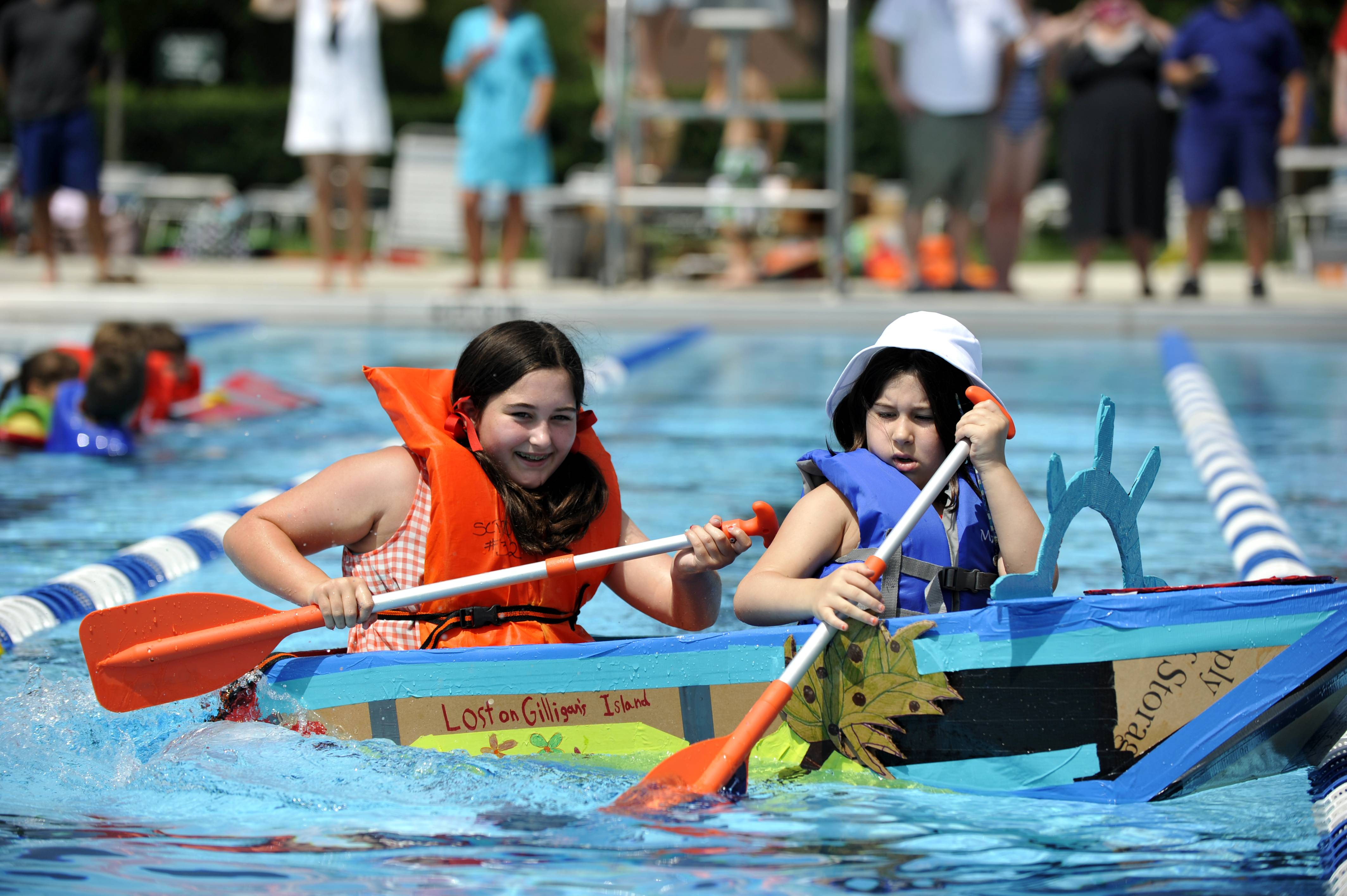 "Lily Rooney, of St. Charles, 12, left, and her sister Norah, 8, paddle their handmade boat called Gilligan's Island, during the Sink or Swim Cardboard Boat Race at Swanson Pool in St. Charles on Saturday. This was Lily and Norah's first time racing a cardboard boat and they came in first place. Their grandfather, Jim Stevens, helped them construct it and Norah said she thought it was ""fun to be in character."""