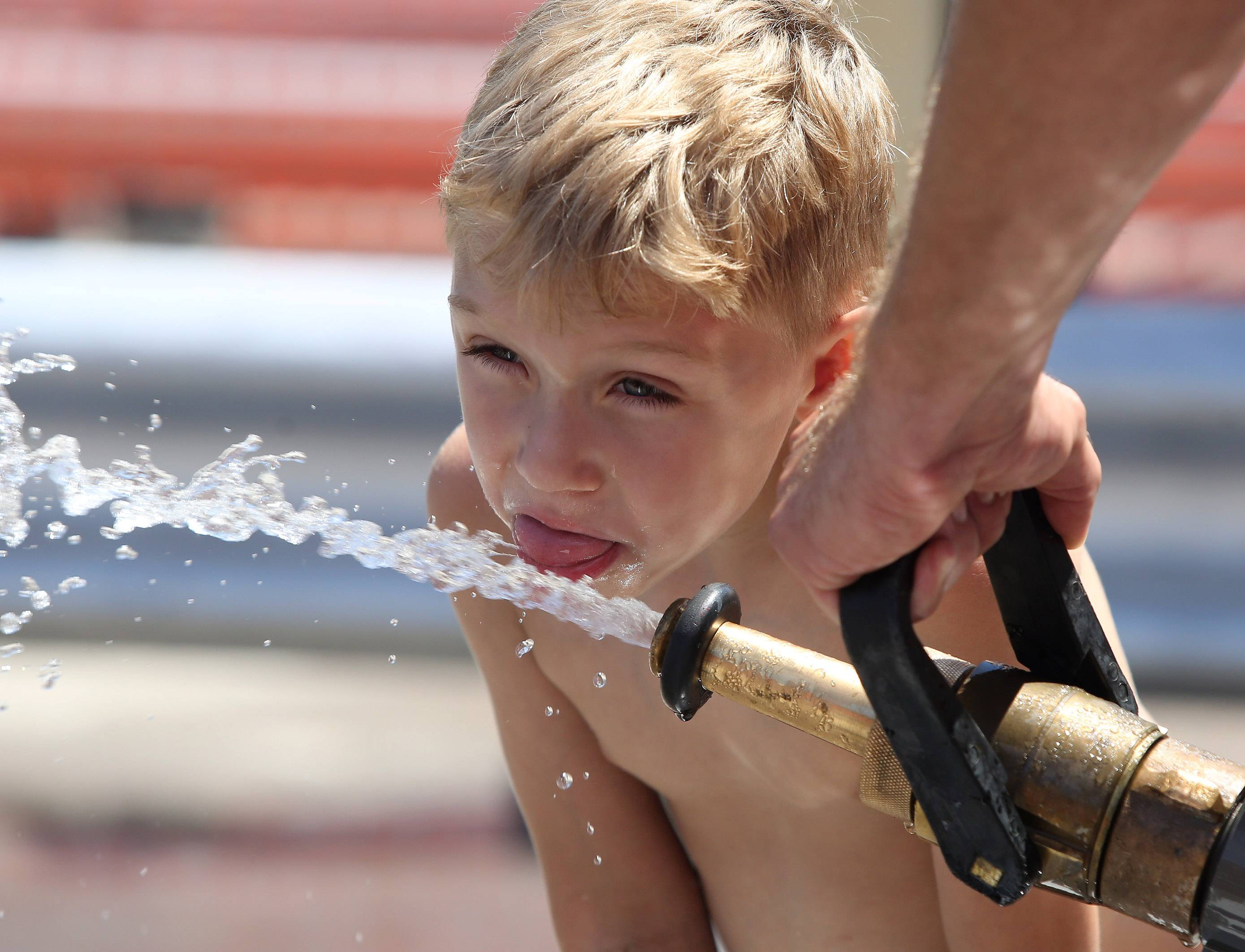Four-year-old Chase Beake, of Round Lake, tries to sip water from a fire hose on a hot afternoon during the water fights Sunday at the Fox Lake Firemen's Festival. Teams representing area businesses competed using high-powered water hoses to blast a barrel across the opponents line.