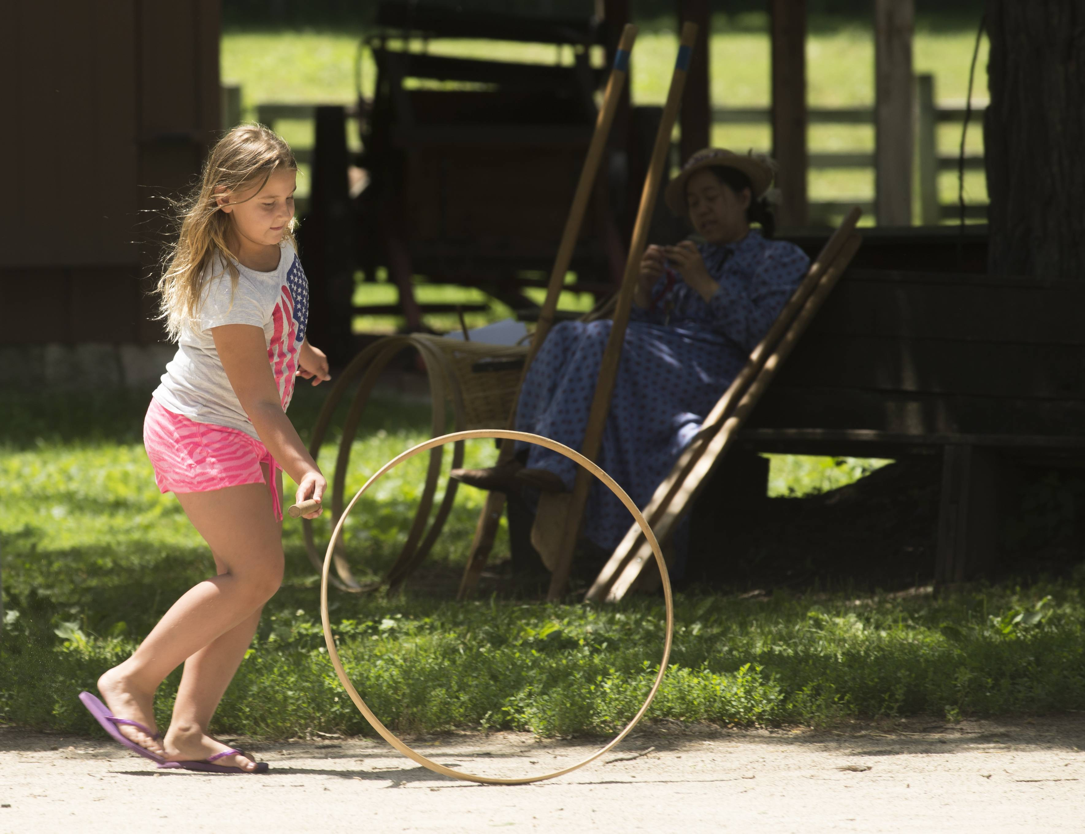 Mia Rosado, 9, of Carol Stream, plays with a hoop and stick just as children in the 1890's did while at the Kline Creek Farm's old-fashioned 4th of July in West Chicago.