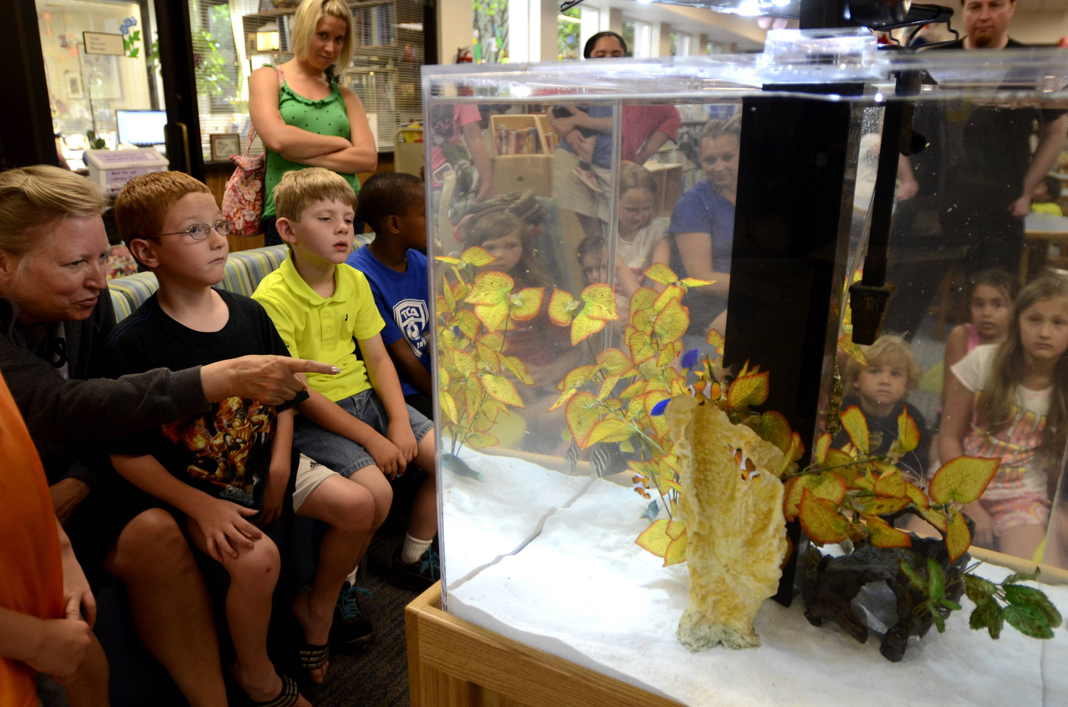 "Tracy Stellato, of St. Charles, points out fish to her son Dillon, 6, left, while children gather around the new aquarium tank during the ""What's in the Aquarium?"" program at the St. Charles Public Library on Monday. The new aquarium was installed on mother's day and children were invited to come and learn about the fish in the youth services area of the library."